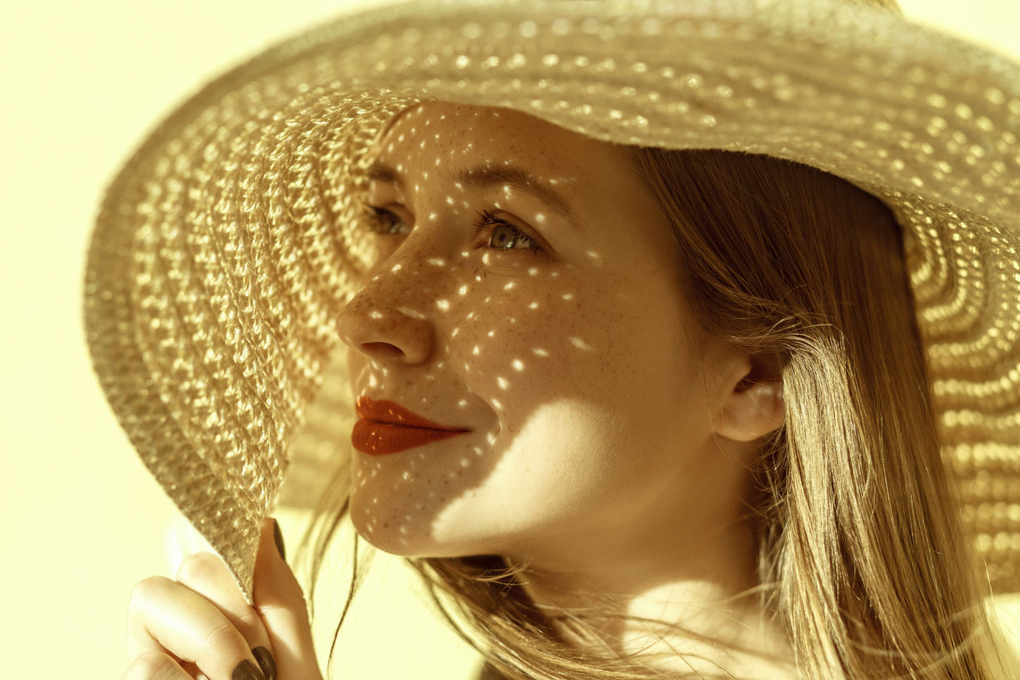 Lady in straw hat in summer. Closeup, portrait of a beautiful and happy freckled woman. Indoor, studio shot. Yellow background