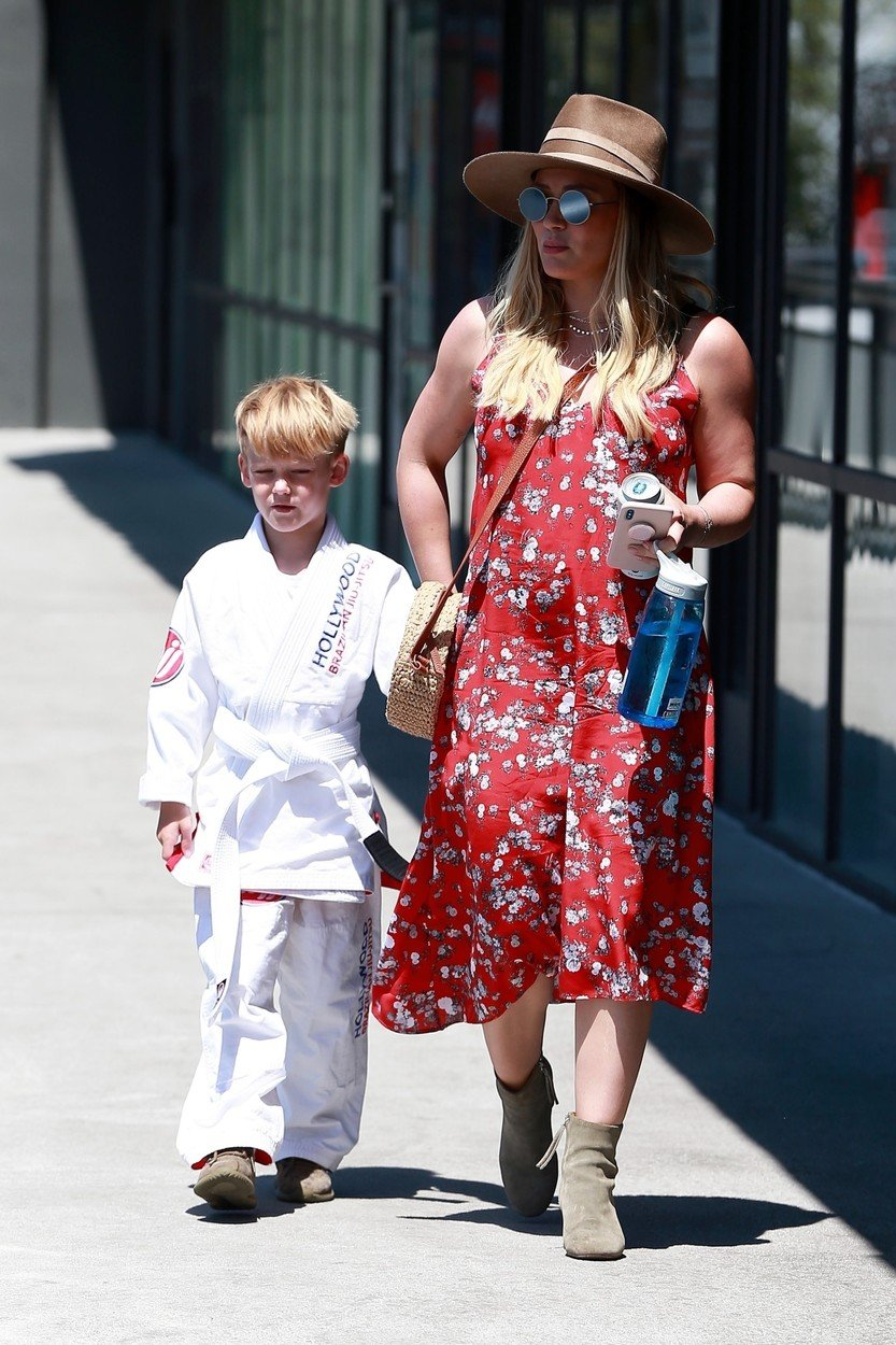 West Hollywood, CA  - Doting mom Hilary Duff takes Luca to a jiu-jitsu class in West Hollywood. The actress looked cute and summery in a red floral dress and wide brimmed hat, while Luca was all business in his jiu-jitsu outfit. Hilary just announced that she is expecting a baby girl with boyfriend Matthew Koma, and she showed a hint of her baby bump  beneath her red dress.  Pictured: Hilary Duff, Luca Comrie    *UK Clients - Pictures Containing Children Please Pixelate Face Prior To Publication*, Image: 374323215, License: Rights-managed, Restrictions: , Model Release: no, Credit line: Profimedia, AKM-GSI