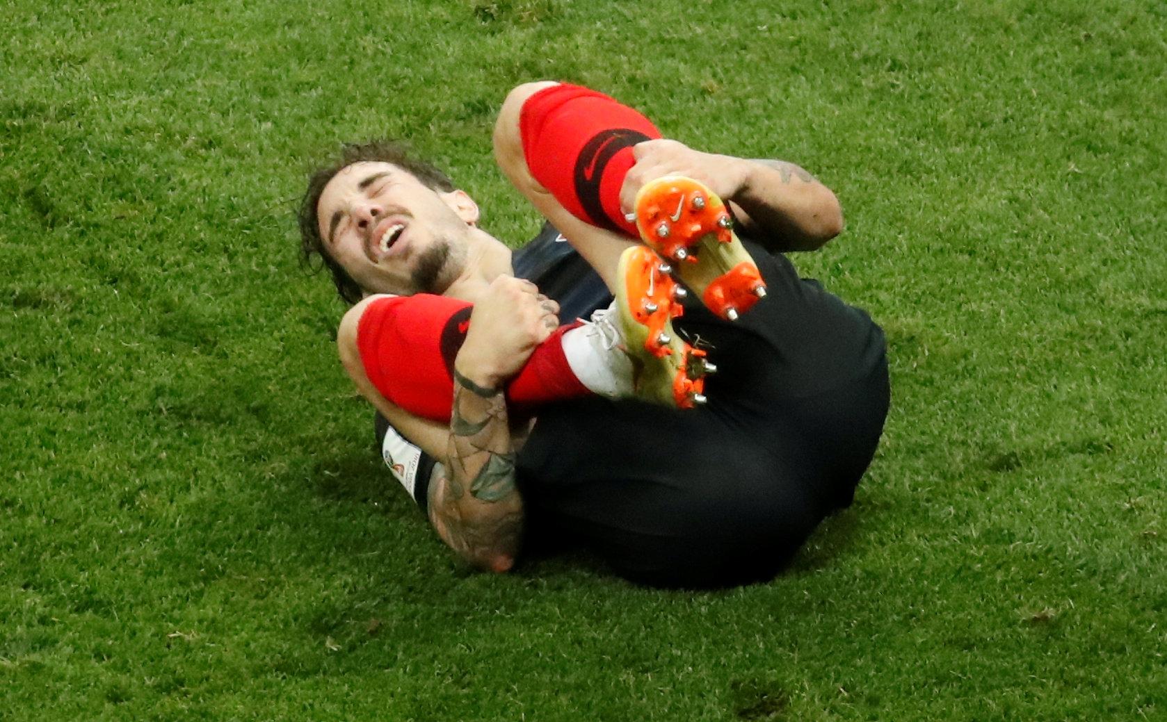 Soccer Football - World Cup - Semi Final - Croatia v England - Luzhniki Stadium, Moscow, Russia - July 11, 2018  Croatia's Sime Vrsaljko reacts as he holds his leg                                       REUTERS/Christian Hartmann