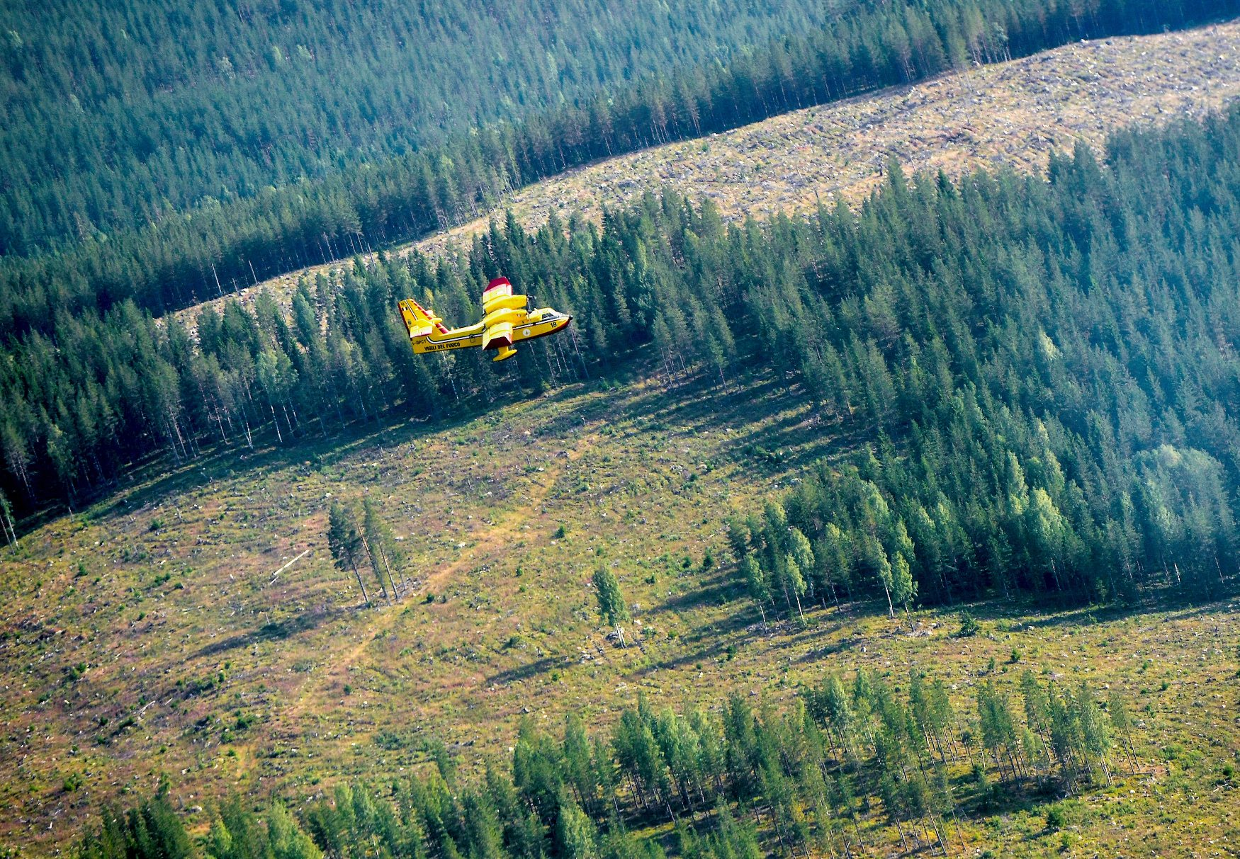 An Italian Bombardier CL-415 SuperScooper flies towards a wildfire outside Ljusdal, Sweden,  July 18, 2018. TT News Agency/Maja Suslin via REUTERS  ATTENTION EDITORS - THIS IMAGE WAS PROVIDED BY A THIRD PARTY. SWEDEN OUT. NO COMMERCIAL OR EDITORIAL SALES IN SWEDEN.