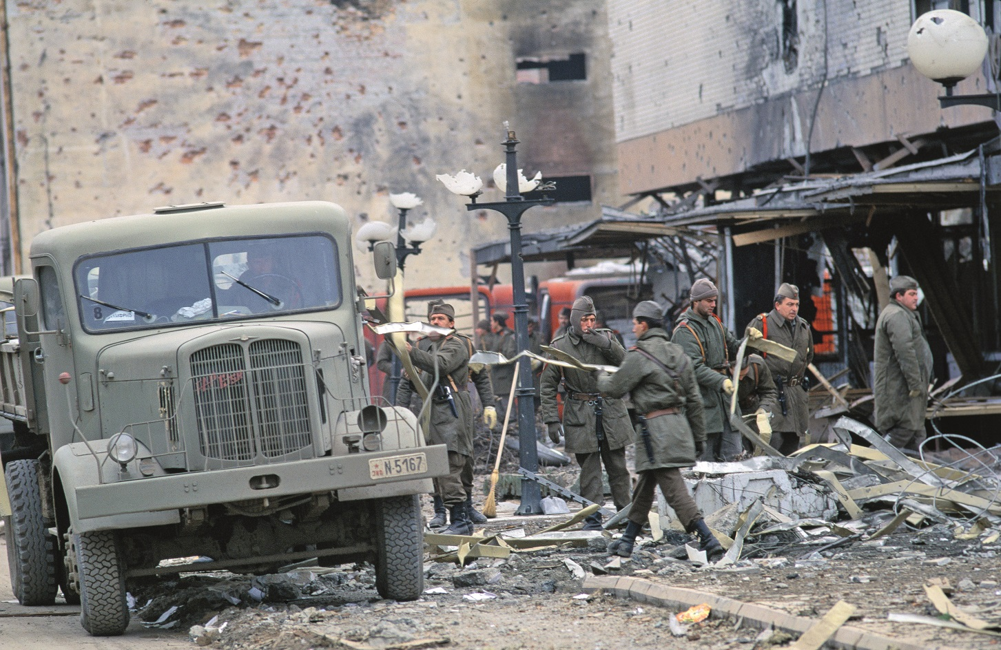 Yugoslavian soldiers remove rubble from the streets after fighting with the Serbian militia in Erdut during the Yugoslavian Civil War. In June of 1991, the territories Croatia and Slovenia declared independence from Yugoslavia, sparking years of violent civil war that killed over 200,000 people and displaced nearly two million. (Photo by Antoine GYORI/Sygma via Getty Images)