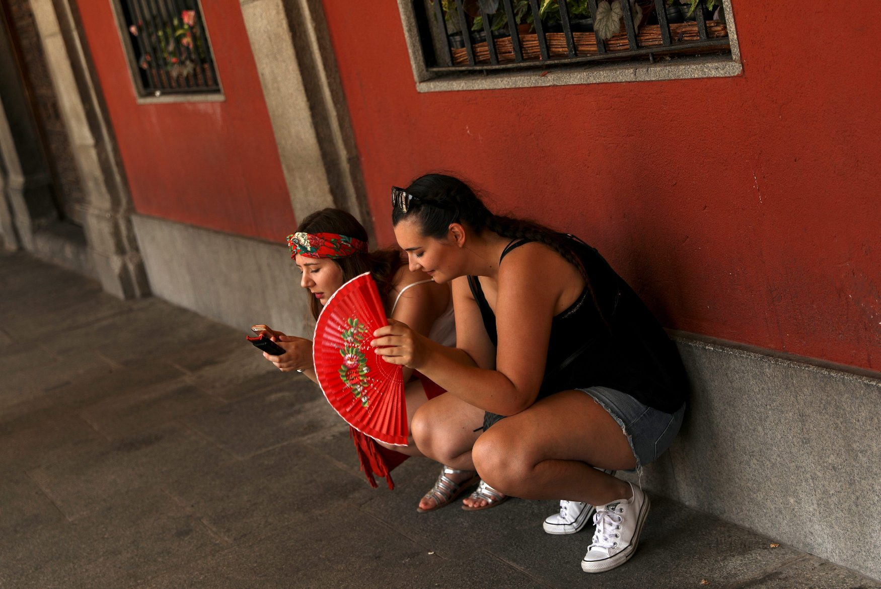 Tourists rest in the shade as temperatures soar throughout the country, in Madrid, Spain, August 2 2018. REUTERS/Susana Vera