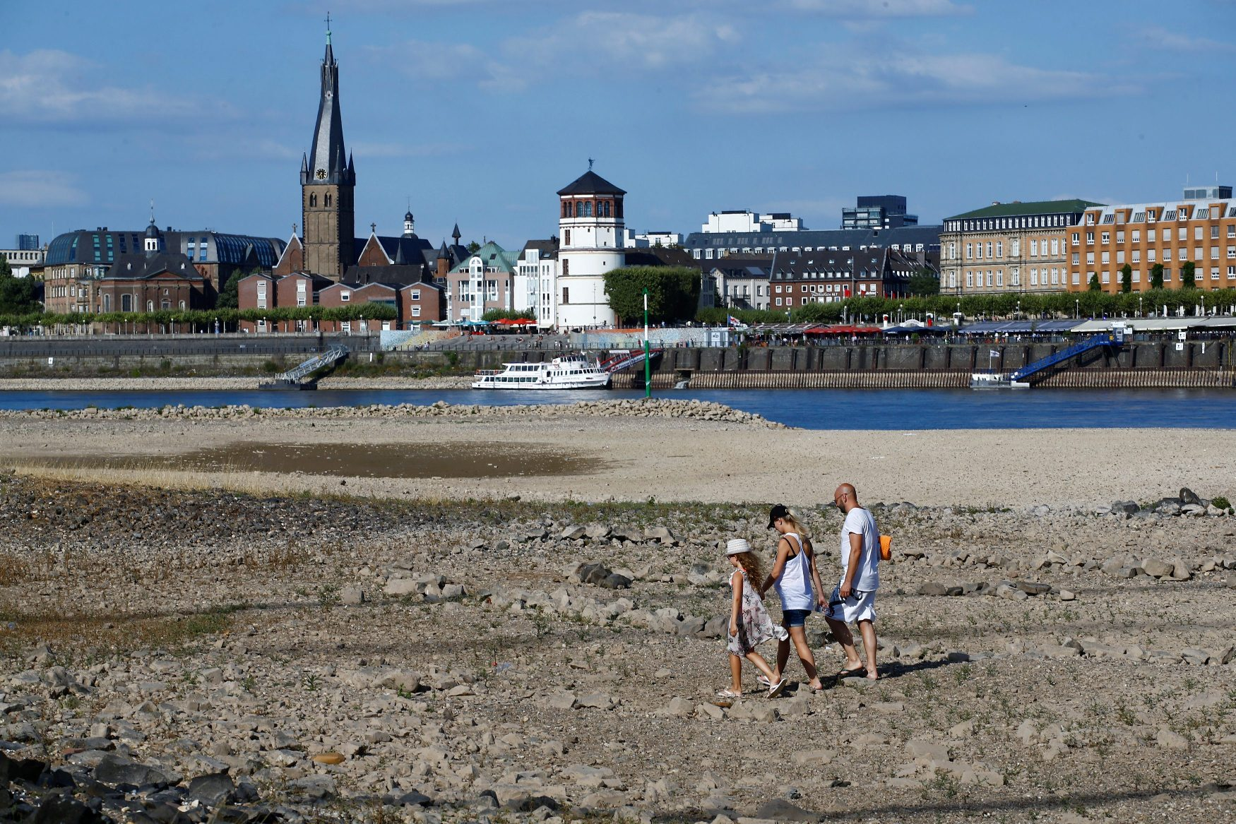 A family walks through the partially dried riverbed of Europe's most important waterway, Rhine in front of the skyline of Dusseldorf, Germany, July 31, 2018. Water levels remain low as a drought and heatwave continues and freight vessels cannot sail fully loaded on the river. REUTERS/Wolfgang Rattay