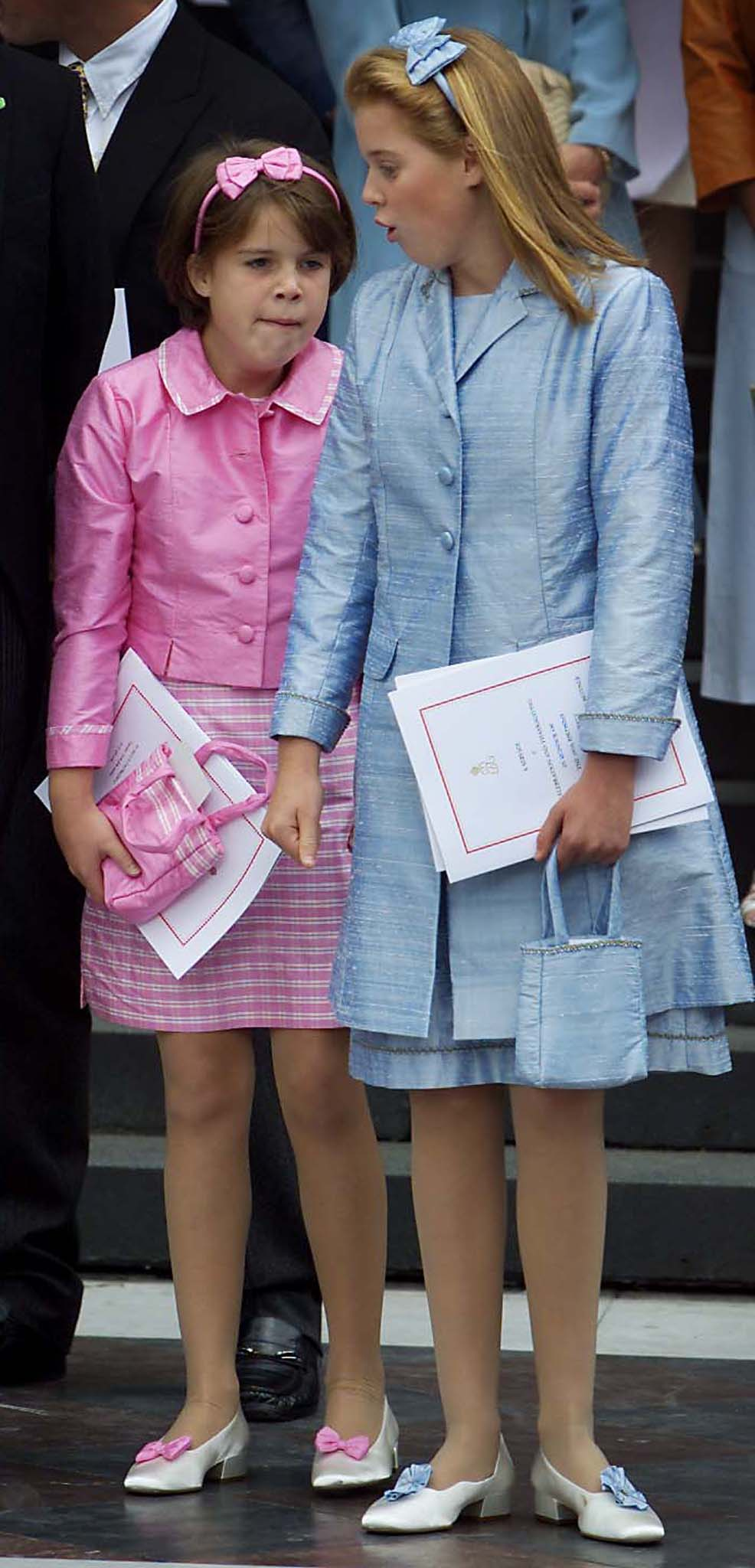 Princesses Eugenie (R) and Beatrice wait for their car on the steps of St Pauls Cathedral following the service of Thanksgiving July 11. The Royal Family were joined by monarchs from around Europe and British centenarians to start a month of celebrations to mark the 100th birthday of the Queen Mother.  JE - RP2DRHZBBZAB