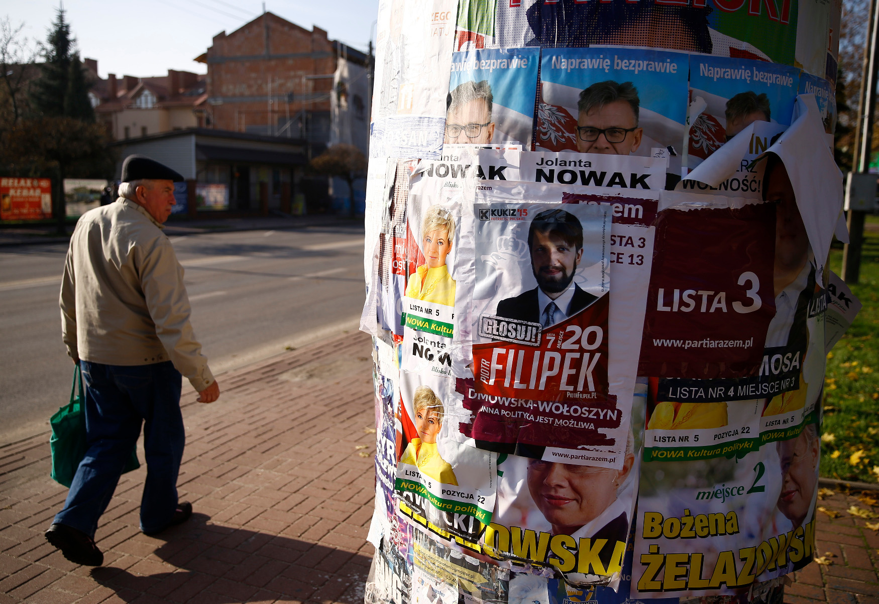 A man walks by an advertising pillar covered with election posters in Radzymin near Warsaw, Poland October 27, 2015. Polish eurosceptic, conservative opposition Law and Justice party secured a historic win in Sunday's parliamentary election, final results showed on Tuesday, unseating the centrist Civic Platform after an eight-year rule. REUTERS/Kacper Pempel  - LR1EBAR14SPNV
