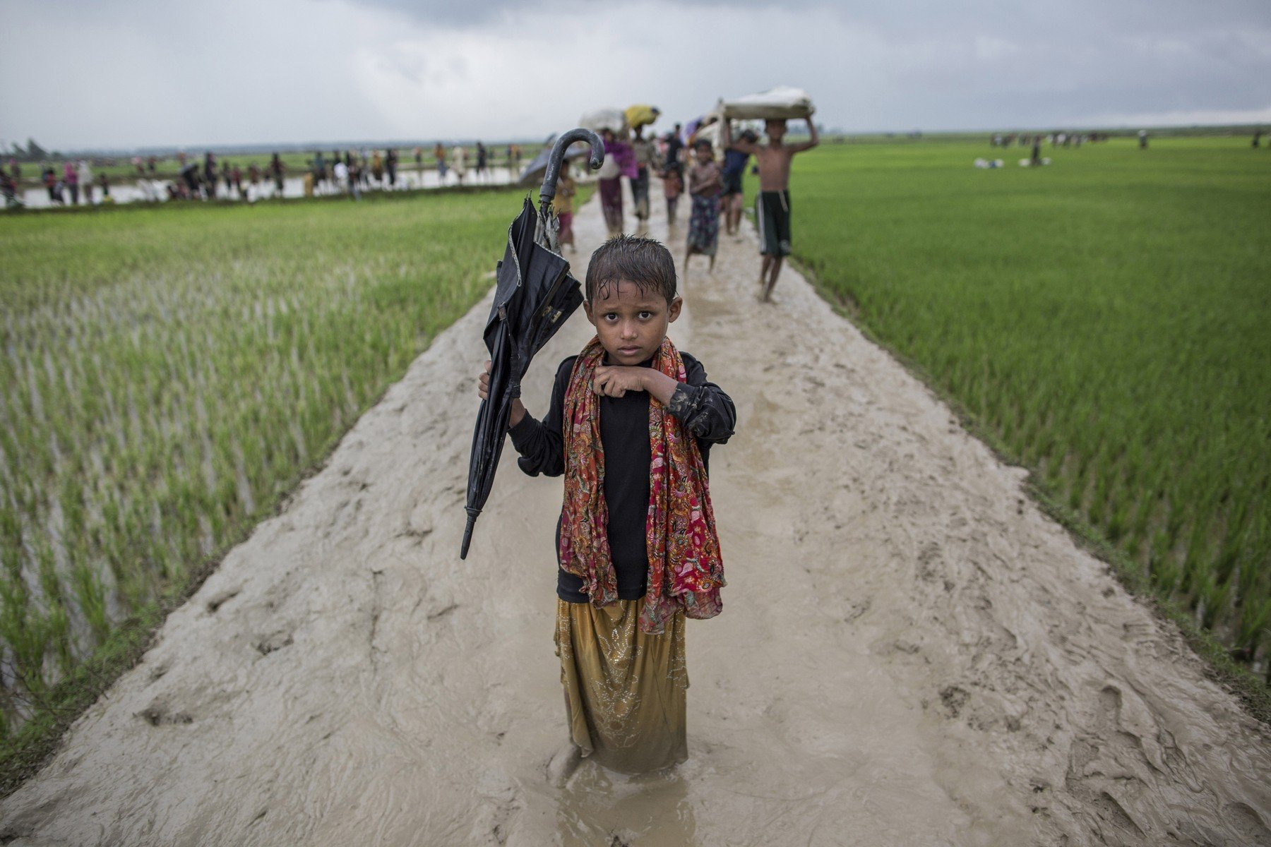 September 3, 2017 - Cox'S Bazar, Chittagong, Bangladesh - Asma, 9, from Myanmar who has crossed the border with her parents into Bangladesh on 3 September, after three days of walking to escape violence in her village..In a grueling journey to cross into safety, the strongest carry the weakest in the damp paddy fields and heavy monsoon rainfall. The rain is heavy and frequent, and makes the ground incredibly wet and muddy, thus making it even more difficult to walk through. The journey to Bangladesh was hard for the Rohingya refugees, especially because there were many children and elderly people fleeing as well. They have to cross the land-mine infested border between Myanmar and Bangladesh to reach safety; while others take the risk of traveling in unstable fishing boats. More than 650,000 Rohingya refugees have fled from violence in Myanmar since August 25, 2017. I chose to make portraits so as to capture the juxtaposition of their exhausted faces, as well as the look of relief on their faces, after safely crossing the border., Image: 372741047, License: Rights-managed, Restrictions: , Model Release: no, Credit line: Profimedia, Zuma Press - Archives