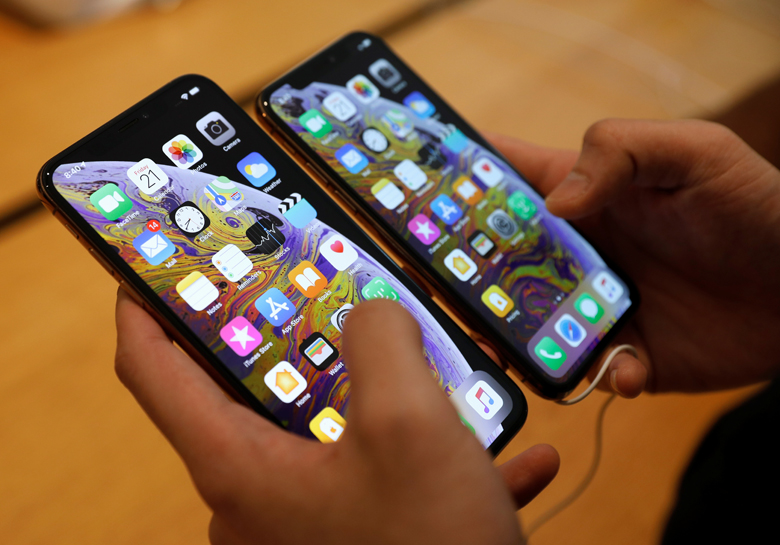 A customer compares the size of the new iPhone XS and iPhone XS Max at the Apple Store in Singapore September 21, 2018. REUTERS/Edgar Su - RC11F423A010