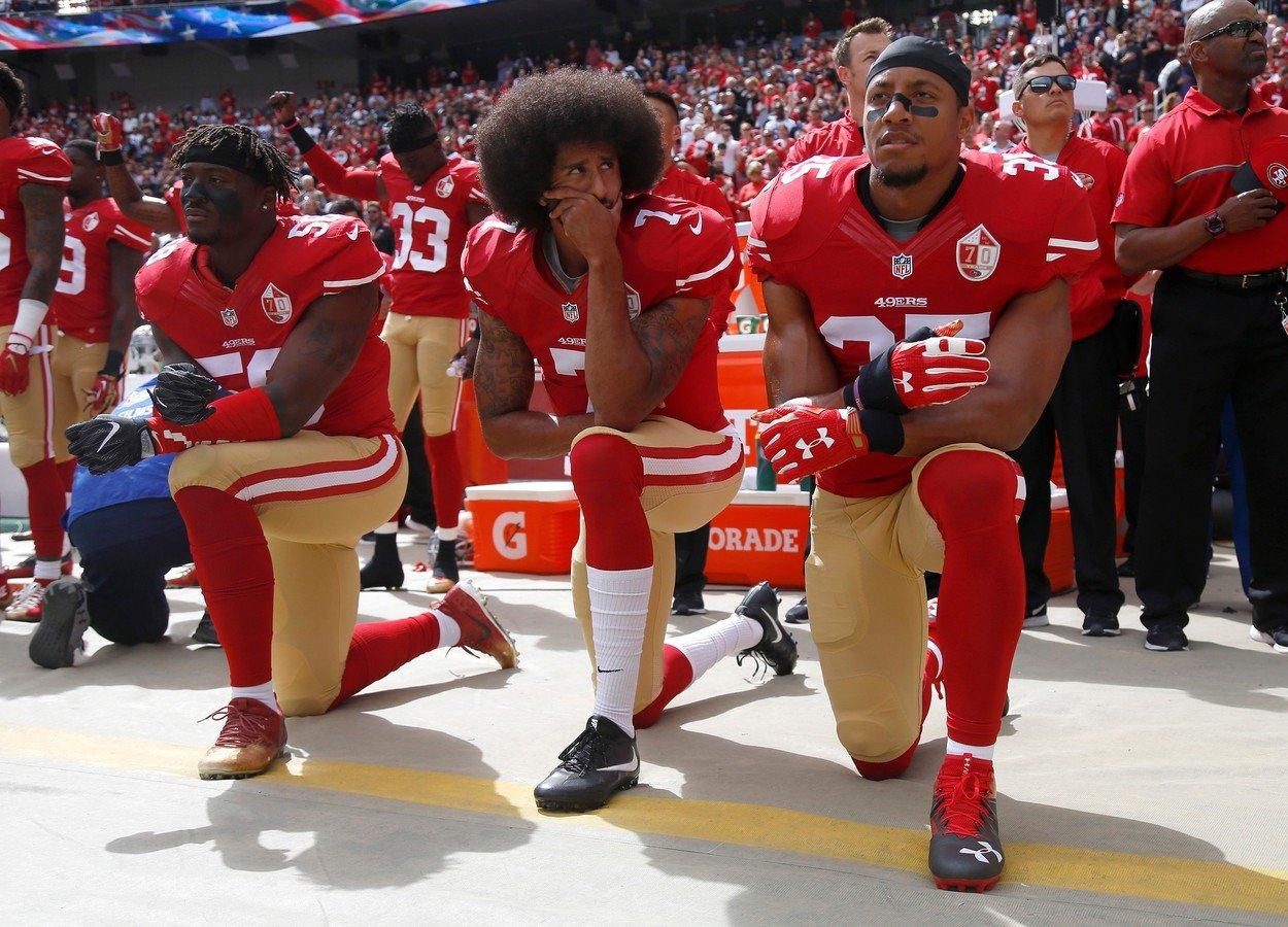 Igrači NFL-a Eli Harold, Colin Kaepernick i Eric Reid kleče za vrijeme američke himne u znak protesta protiv poslicijskog nasilja nad Afroamerikancima