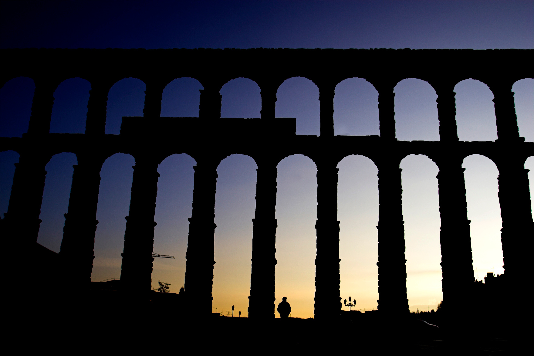 A man passes in front of Segovia's 2,000-year-old Roman aqueduct in central Spain April 8, 2006. Segovia's aqueduct, which stretches from the walls of the old town to the edges of Sierra de Guadarrama, is one of the greatest surviving monuments of Roman engineering. Its construction is considered a masterpiece because its 20,400 stone blocks are not united by mortar or concrete. REUTERS/Victor Fraile BEST QUALITY AVAILABLE - GM1DSIMQSHAA