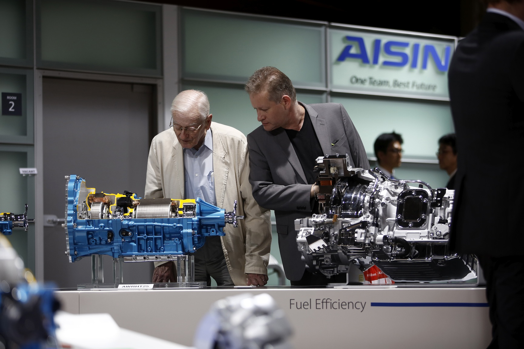 Visitors inspect cutaway hybrid automatic transmission units for fuel efficiency, including a AWRHT25 assembly, left, as they sit on display during the first preview day at the Paris Motor Show in Paris, France, on Thursday, Oct. 2, 2014. The show, also known as Mondial de L'Automobile, runs from Oct. 4 through Oct. 19 and showcases 250 automobile manufacturers from 18 countries. Photographer: Simon Dawson/Bloomberg via Getty Images