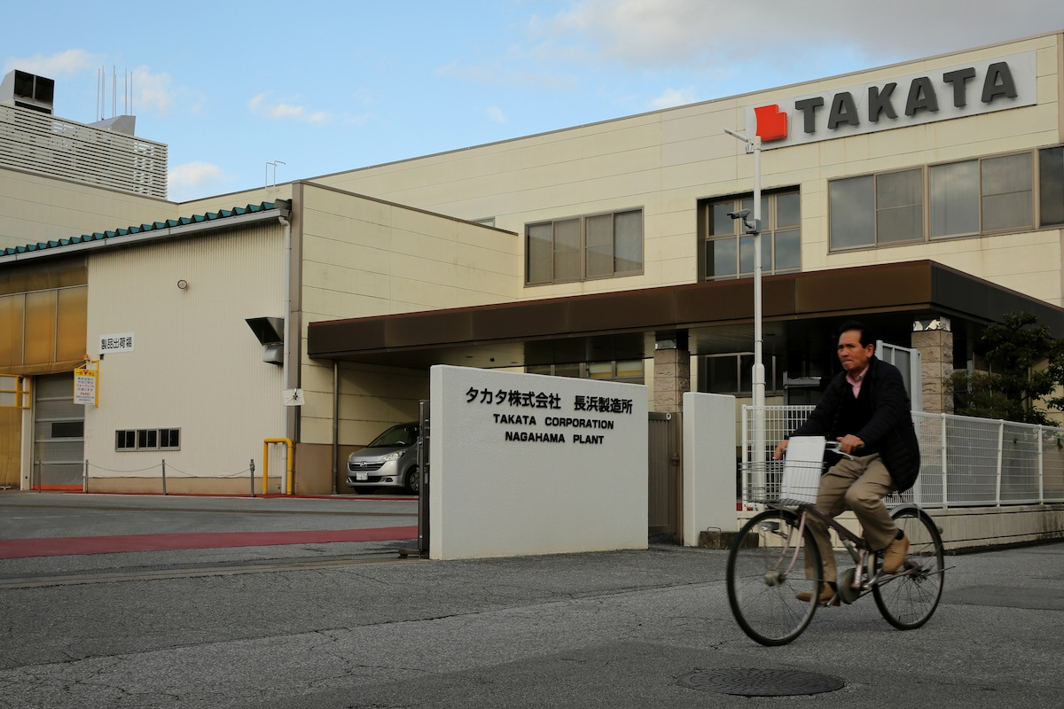 A man rides a bicycle past the entrance to Takata Corp.'s Nagahama plant in Nagahama, Shiga, Japan, on Friday, Nov. 25, 2016. Takata's selection of a bidder is running behind schedule as the shortlisted companies embark on a more thorough review of the air-bag maker behind the biggest auto safety recall, according to people familiar with the matter. Photographer: Buddhika Weerasinghe/Bloomberg via Getty Images