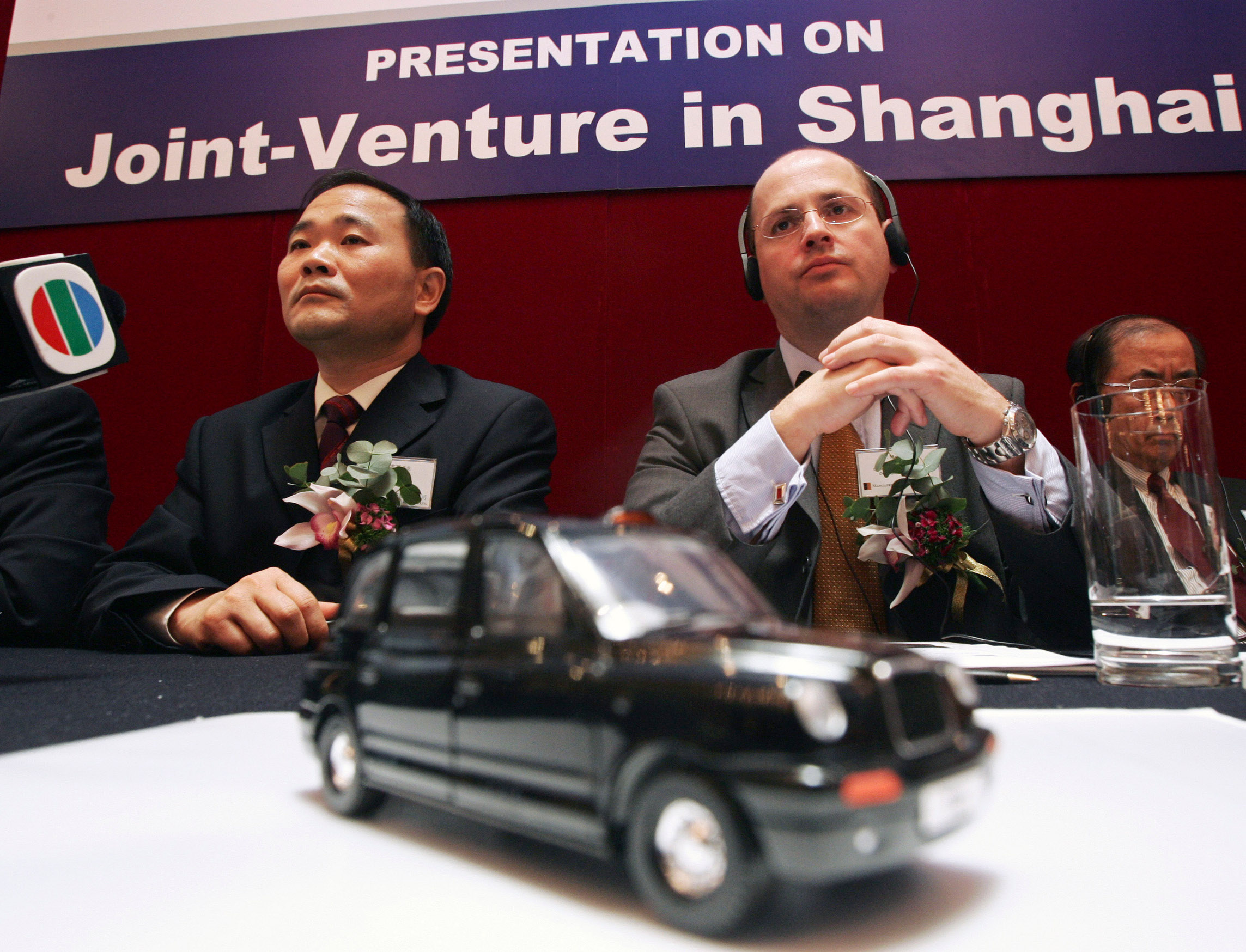 Li Shu Fu (L), Chairman of Geely Automobile Holdings Ltd., and Mark Fryer, Group Finance and Business Development Director of Manganese Bronze Holdings Plc., attend a signing ceremony as they establish a joint venture company to produce London taxis in Hong Kong November 9, 2006. REUTERS/Paul Yeung  (CHINA) - GM1DTXEDLZAA