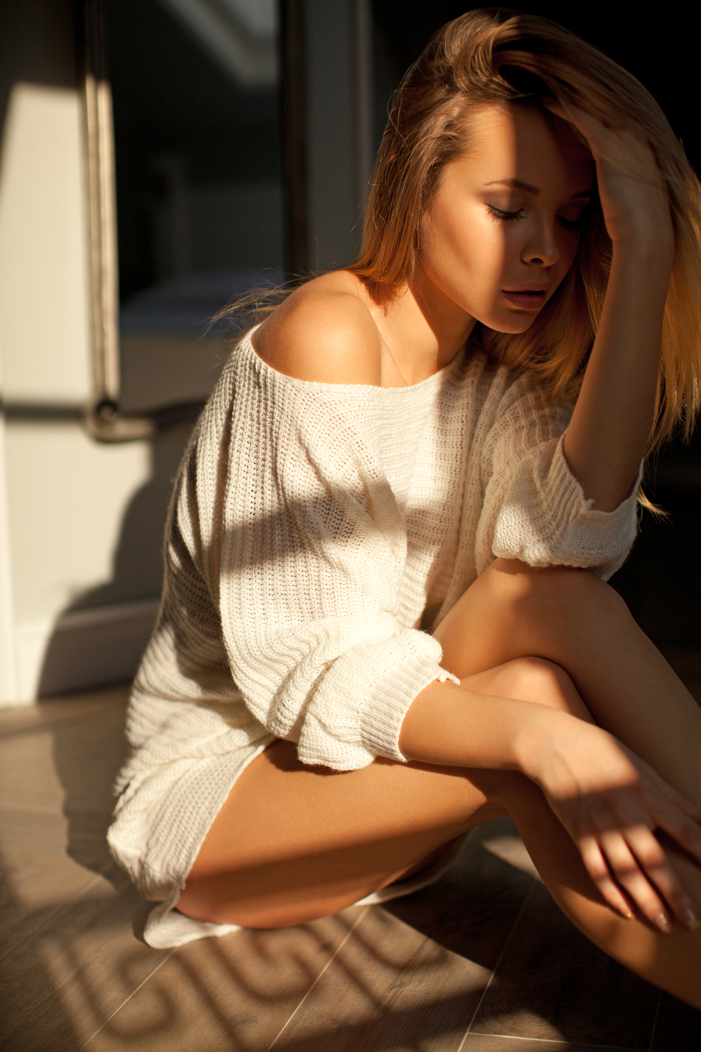 Beautyful young blond woman sitting on the floor and wearing white casual sweater. She is very sensual and attractive.