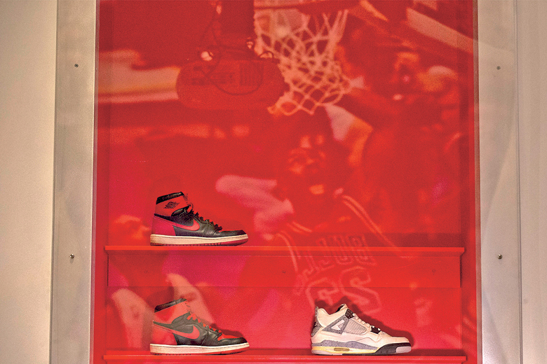 Air Jordan sneakers are displayed while a photo of Michael Jordan is reflected in the glass during a preview for