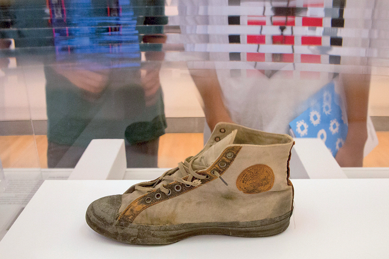 Visitors look at a Converse sneaker from 1917 during the preview for