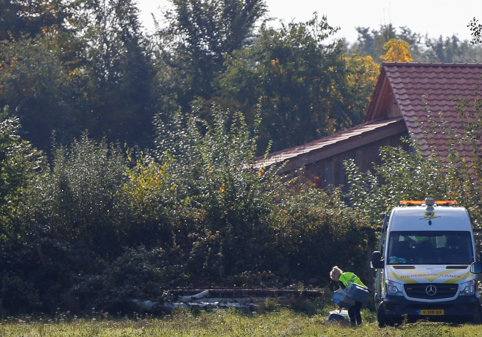 A woman from animal ambulance holds cat carriers at the site of a remote farm where a family spent years locked away in a cellar, according to Dutch broadcasters' reports, in Ruinerwold, Netherlands October 16, 2019. REUTERS/Eva Plevier