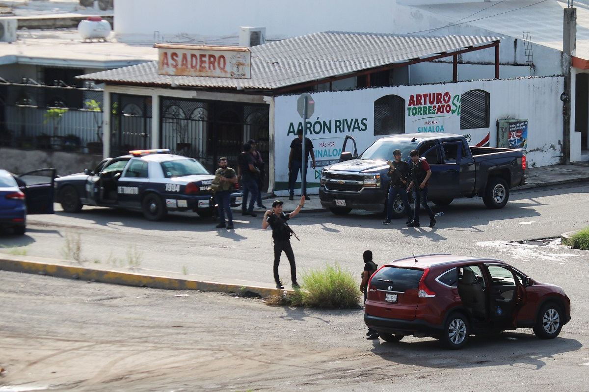 Cartel gunmen are seen on a street during clashes with federal forces following the detention of Ovidio Guzman, son of drug kingpin Joaquin