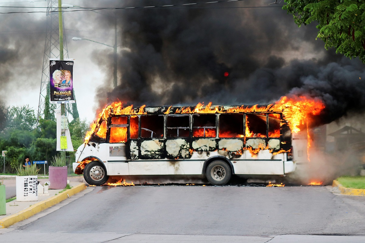 A burning bus, set alight by cartel gunmen to block a road, is pictured during clashes with federal forces following the detention of Ovidio Guzman, son of drug kingpin Joaquin