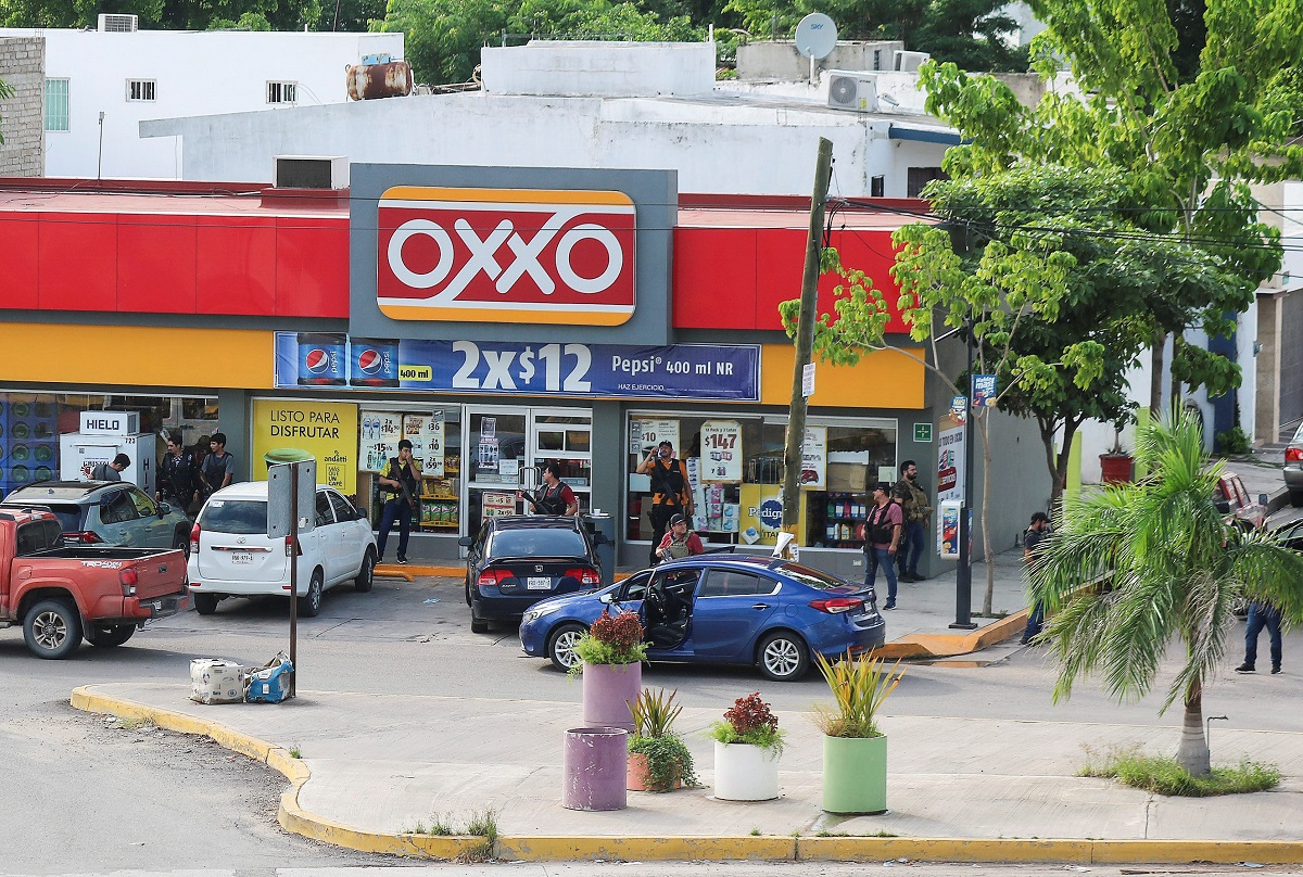 Cartel gunmen stand outside a store during clashes with federal forces following the detention of Ovidio Guzman, son of drug kingpin Joaquin
