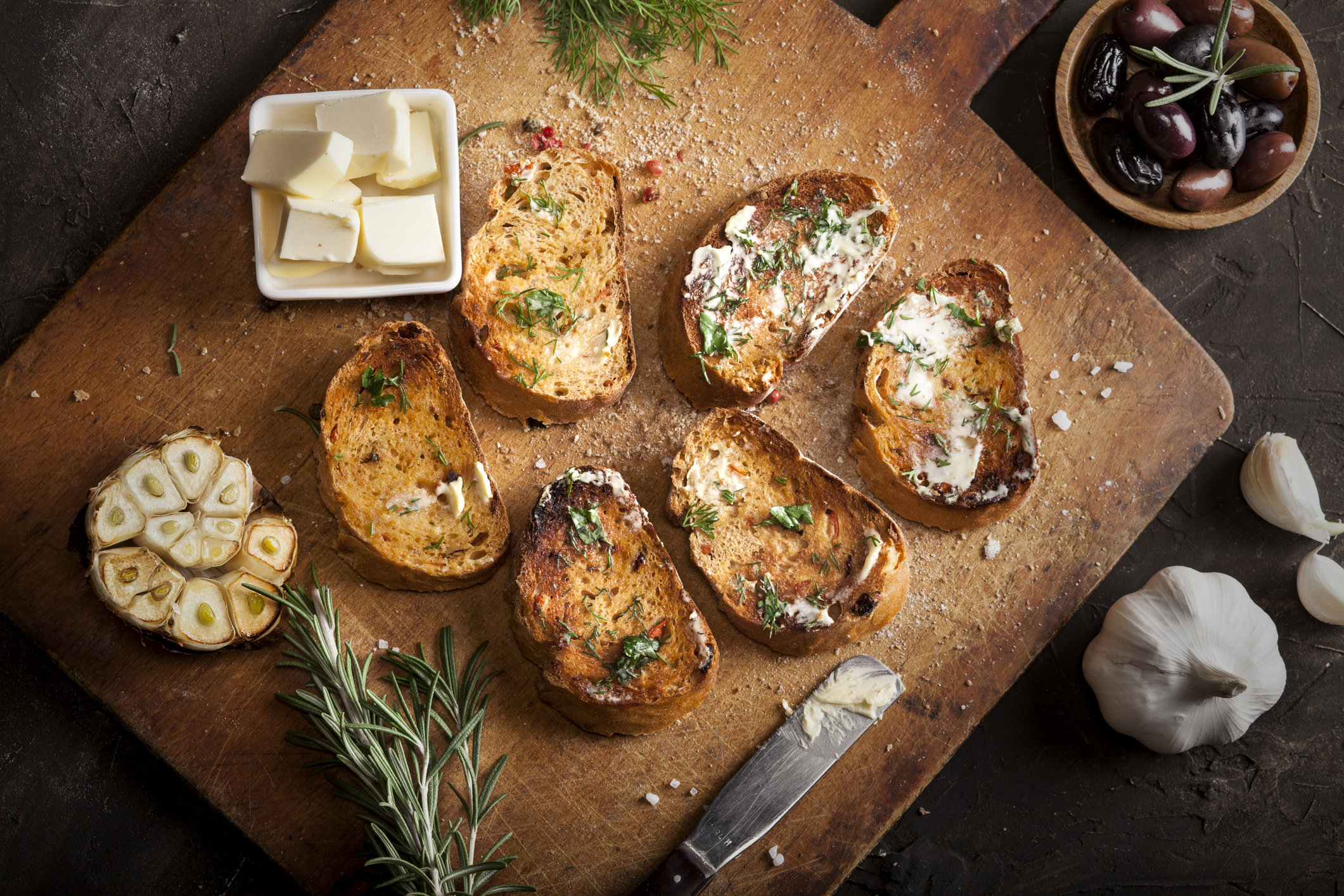 Sliced traditional toast bread with butter, olives, garlic and herbs on a cutting board and dark table with. Top view.