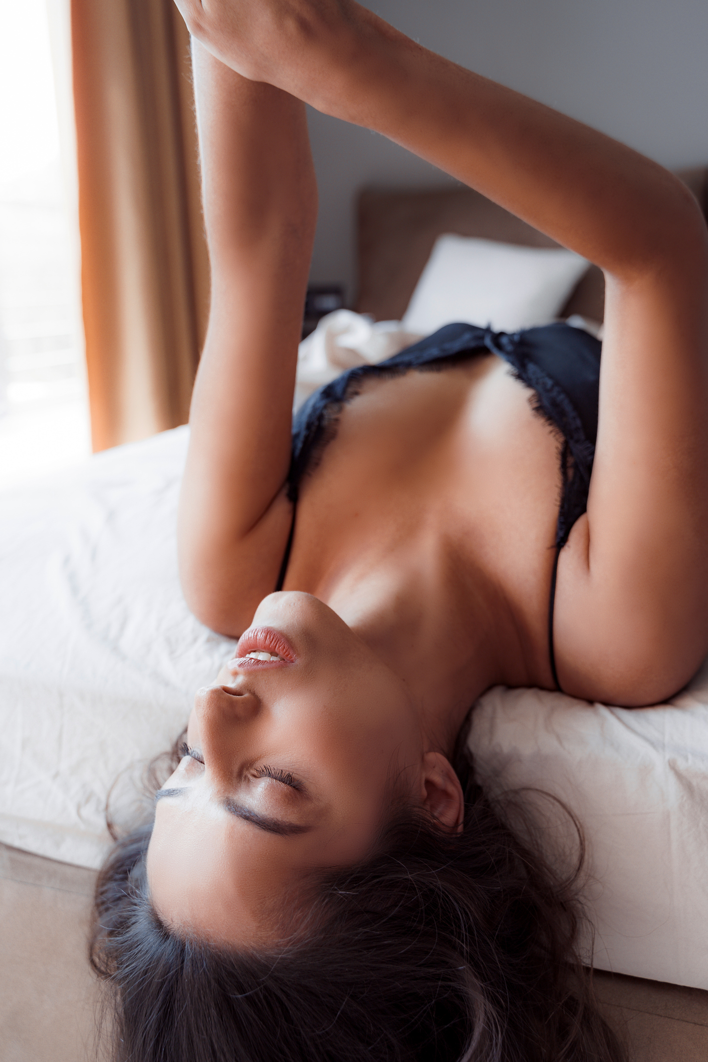 Gorgeous young woman lying alone in her bed with her hands up