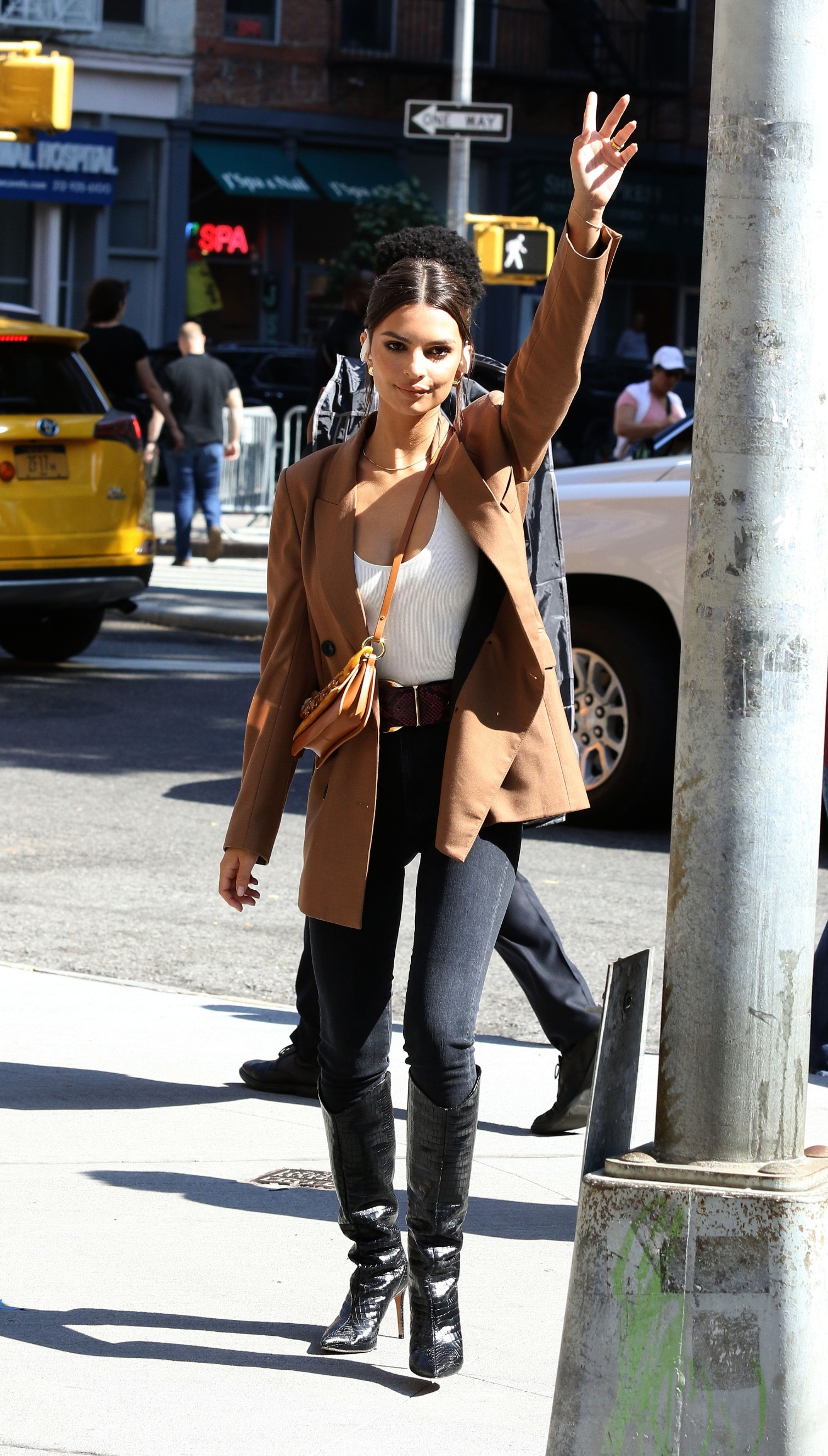 Emily Ratajkowski hails a taxi while filming a