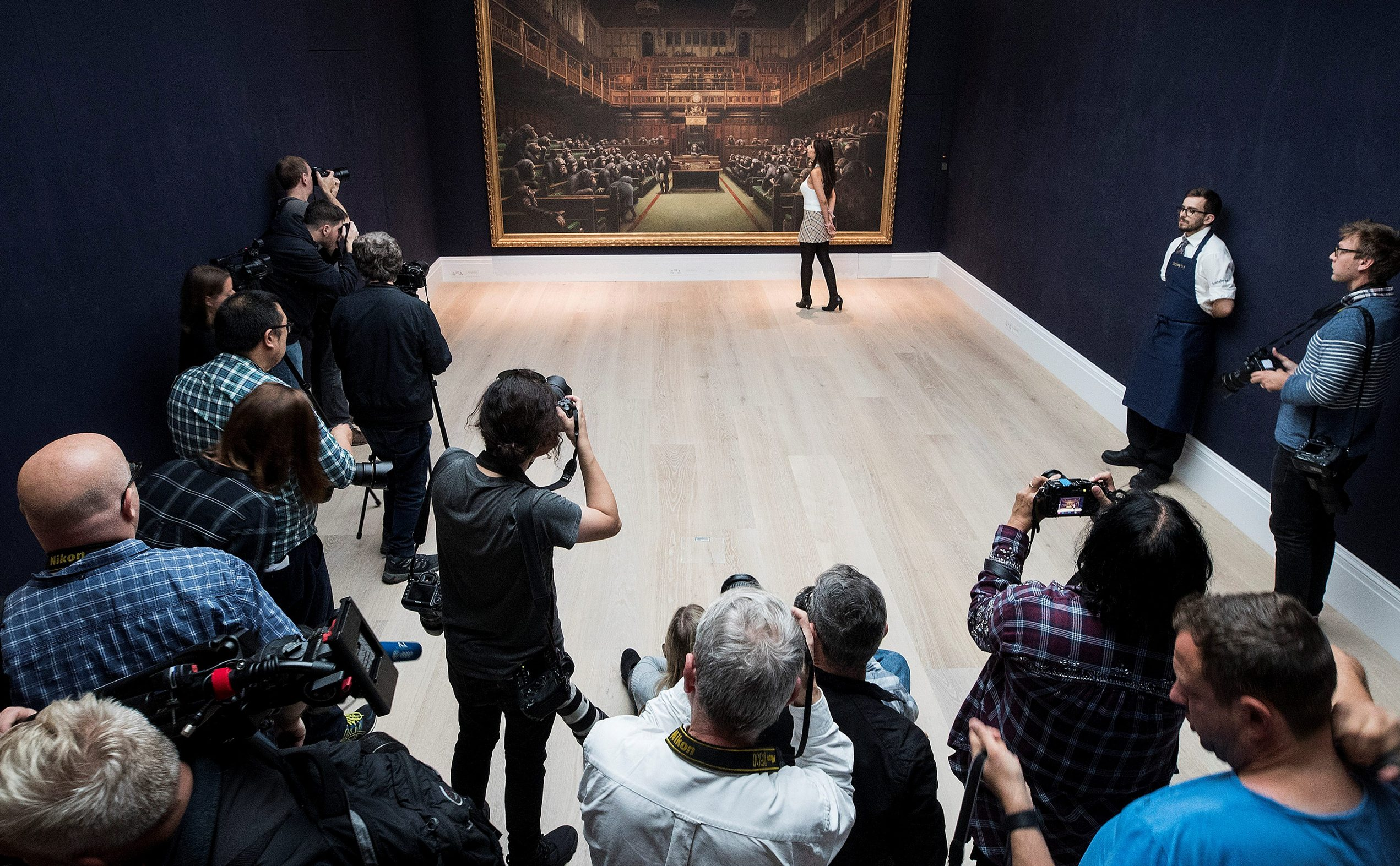 Members of the media take photos as a Sotheby's staff poses for a photograph with Banksy's 'Devolved Parliament' which has an estimated value of 1.5-2 million British pounds in a forthcoming sale in London, Britain September 27, 2019. REUTERS/Simon Dawson