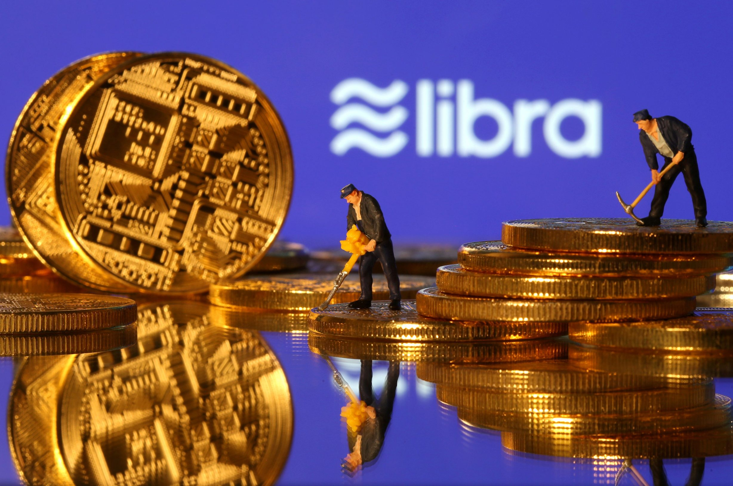 FILE PHOTO: Small toy figures are seen on representations of virtual currency in front of the Libra logo in this illustration picture, June 21, 2019. REUTERS/Dado Ruvic/Illustration/File Photo