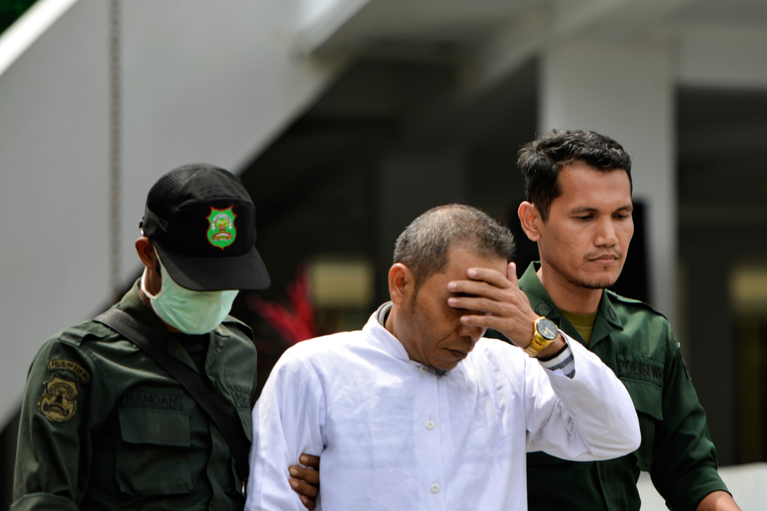 Aceh Ulema Council (MPU) member Mukhlis (C) is escorted by members of the Sharia police before being whipped in public in Banda Aceh on October 31, 2019. An Indonesian man working for an organisation which helped draft strict religious laws ordering adulterers to be flogged was himself publically whipped on October 31 after he was caught having an affair with a married woman., Image: 480105580, License: Rights-managed, Restrictions: , Model Release: no, Credit line: CHAIDEER MAHYUDDIN / AFP / Profimedia