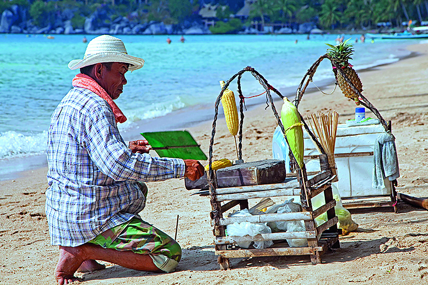 Beach vendor preparing corn on tiny portable barbecue on the island Ko Tao / Koh Tao, part of the Chumphon Archipelago in Southern Thailand. (Photo by: Arterra/Universal Images Group via Getty Images)