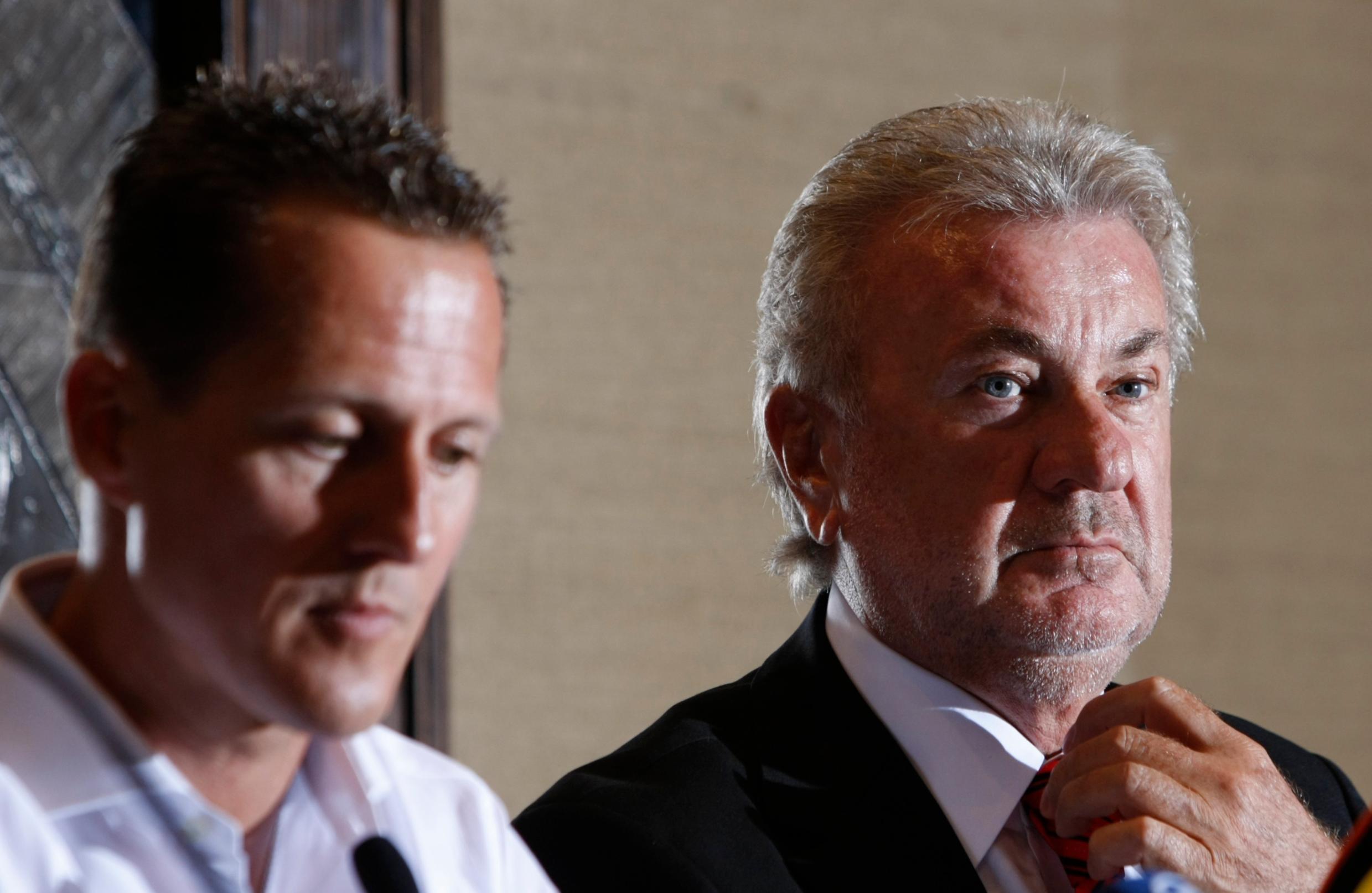 Michael Schumacher i Wilhelm Weber fotografirani 2009. godine na konferenciji za medije na kojoj je Schumacher zbog zdravstvenih problema odgodio povratak Formulu 1