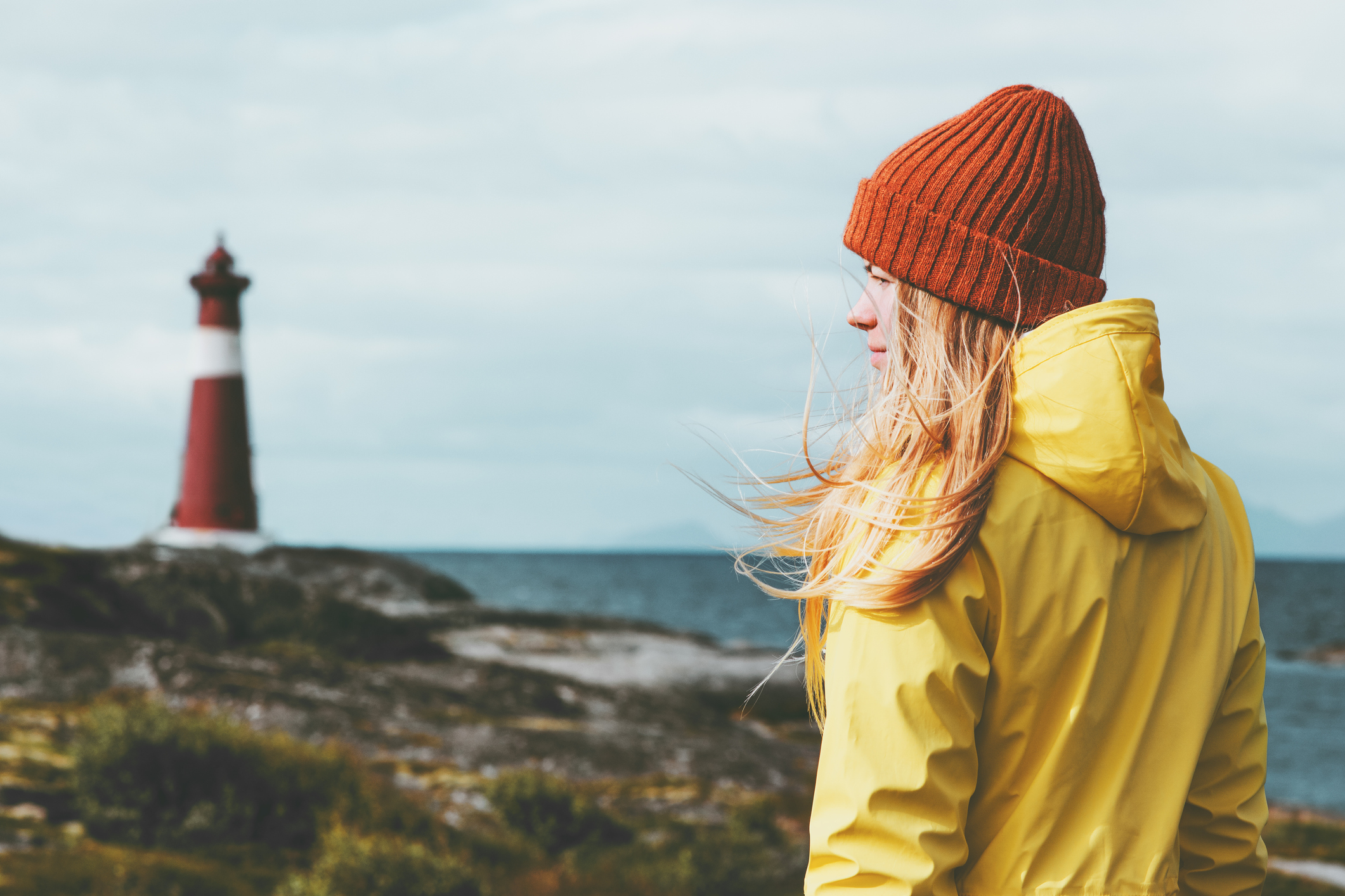Woman sightseeing lighthouse sea landscape in Norway Travel Lifestyle concept scandinavian vacations outdoor. Blonde girl hair on wind wearing orange hat and yellow raincoat