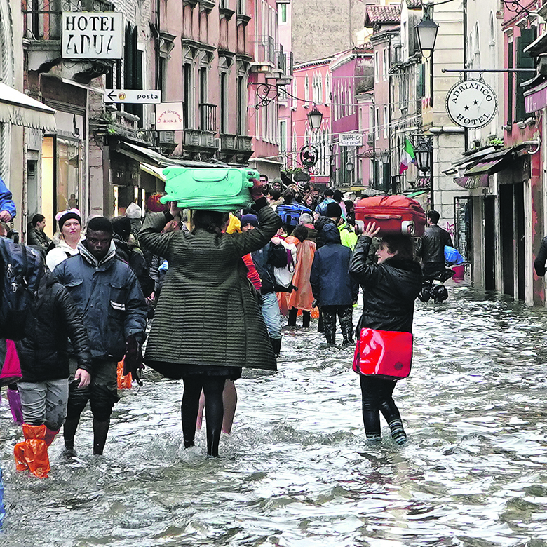 VENICE, ITALY - NOVEMBER 15: People walk in the high water days after the second highest tide from 1966 on November 15, 2019 in Venice, Italy.  More than 80 percent of the city was flooded after Tuesday's high tide of 187cm, the highest level in more than 50 years, leading the government to declare a state of emergency. A second high tide on Friday meant that the iconic St. Mark's Square would remain closed, along with many shops and schools. (Photo by Vittorio Zunino Celotto/Getty Images)