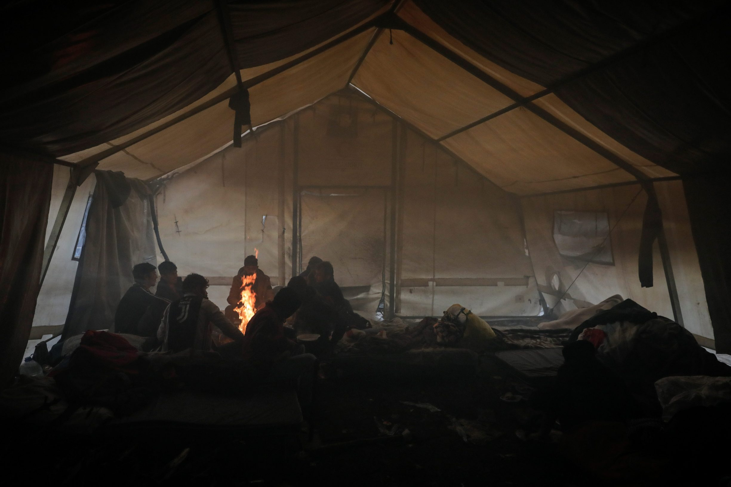 Migrants warm themselves by the fire inside their tent inside Vucjak camp near Bihac, Bosnia and Herzegovina, November 13, 2019. Picture taken November 13, 2019. REUTERS/Marko Djurica