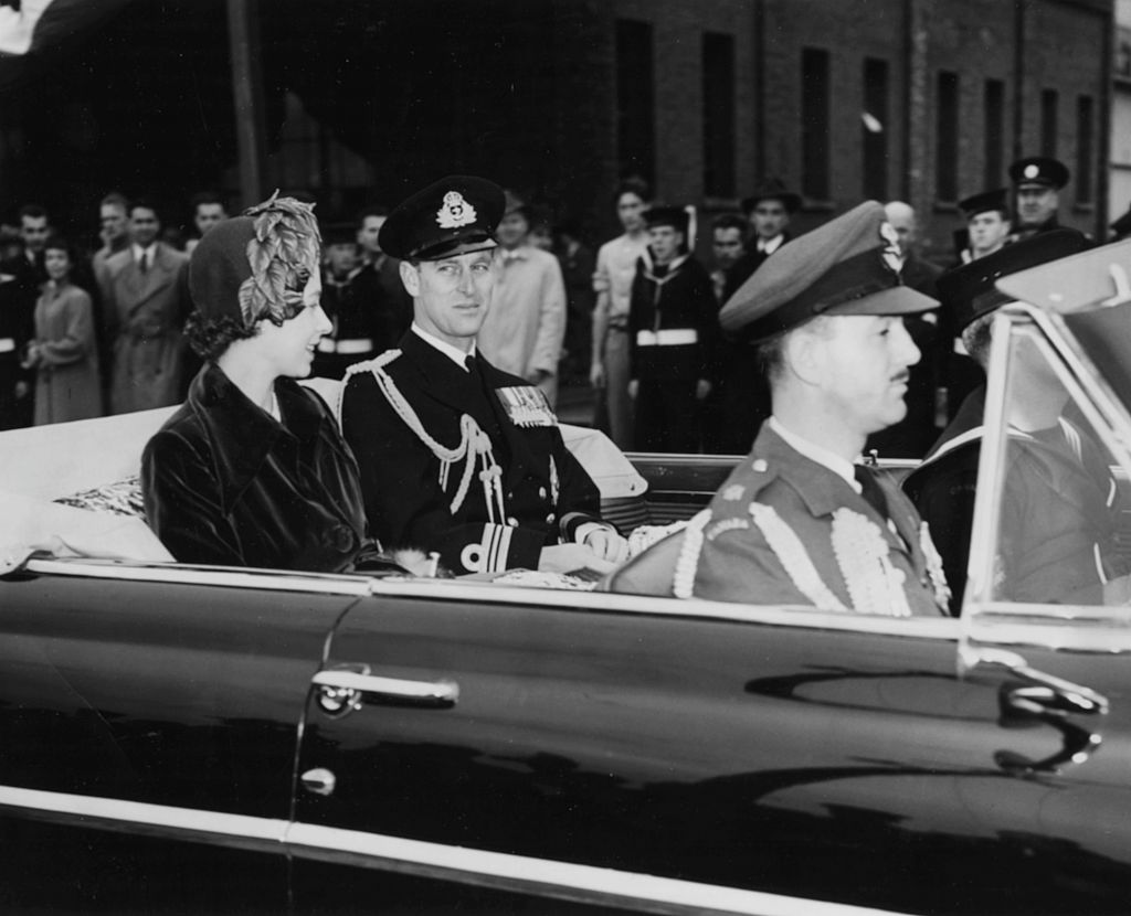 Princess Elizabeth and Prince Philip, the Duke of Edinburgh, riding in the back of their car, with Canadian Air Force Equerry Wing Commander Cox (front), through the crowded streets of Quebec, October 12th 1951. (Photo by Fox Photos/Hulton Archive/Getty Images)