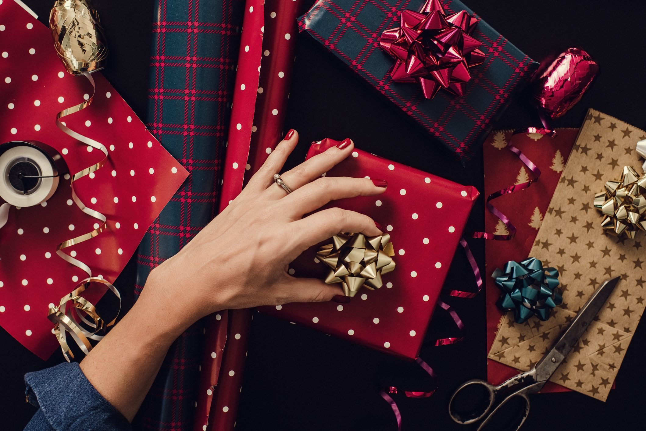 Woman wrapping christmas gifts presents photo taken from above overhead Hands wrapping paper bows. Table top shot taken directly above