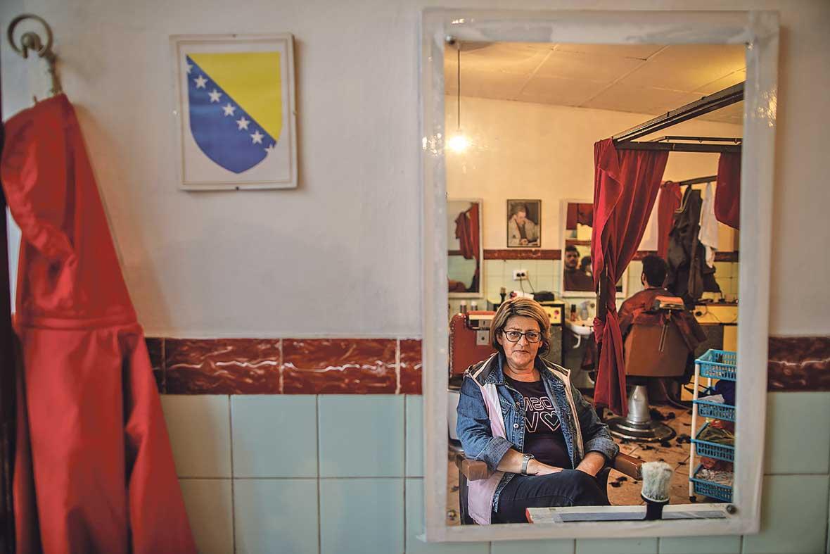 """U centru Bihaća, iza crvenog zastora skoro uvijek navučenog preko izloga, dvanaest vrlo urednih Pakistanaca nabilo se u malu prostoriju od petnaestak kvadrata. Na stolici u kutu sjedi, puši i sluša ih Orana, njihova Mama. Orana je vlasnica malog frizerskog salona, jednog od rijetkih mjesta gdje su migranti dobrodošli i kada nemaju novca ni nekog posebnog posla. """"Meni je njih žao. Kad ih počnu kupiti, ko životinje da kupe. Fuj"""", priča. Iako dosta sugrađana zbog toga negoduje, a neki je po društvenim mrežama i vrlo uvredljivo prozivaju, Oranina vrata su migrantima otvorena otkad je kriza u Bihaću počela. I ona ih ne misli zatvarati, bez obzira na pritiske i kazne kojima joj prijete. Drugi joj se dive. Profesor, stara mušterija još otkad je salon držao Oranin otac, """"prijeti"""" joj da više nikada neće doći ako prestane pomagati migrantima. Hrabra žena je jedan od heroja ove teške priče, i čovjek prije svega. Jedna od rijetkih volontera koje sam u Bihaću sreo, a nije ih malo, koju nije strah da joj se ime i slika pojavi u novinama. Čega je ostale strah? Nas samih?"""