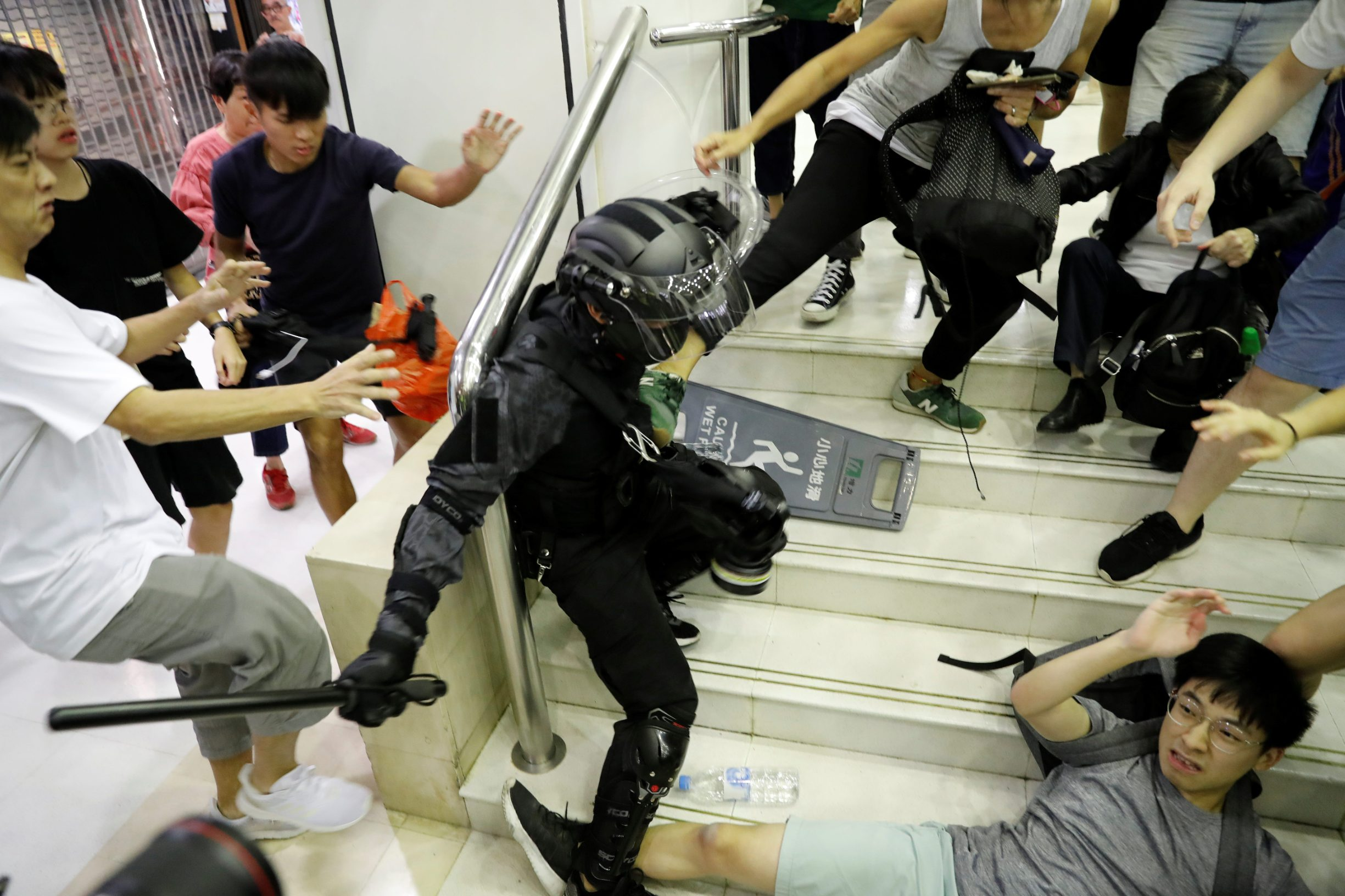People scuffle with a riot police officer at a shopping mall in Tai Po in Hong Kong, China November 3, 2019.  REUTERS/Kim Kyung-Hoon