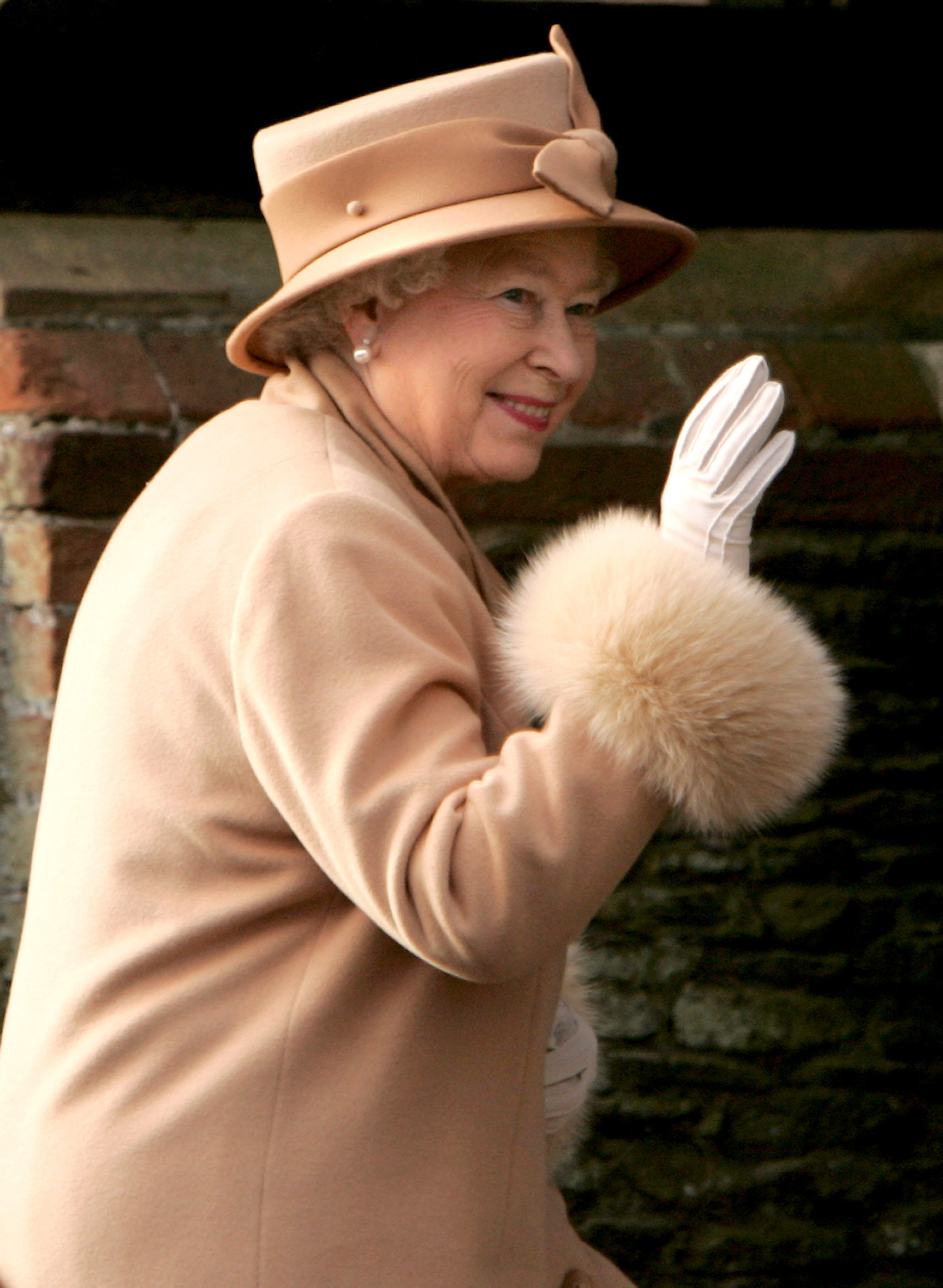 KING'S LYNN, UNITED KINGDOM - DECEMBER 25:  HRH Queen Elizabeth II waves to onlookers as she arrives at the Christmas Day service at Sandringham Church on December 25, 2005 in King's Lynn, England. (Photo by Daniel Berehulak/Getty Images)