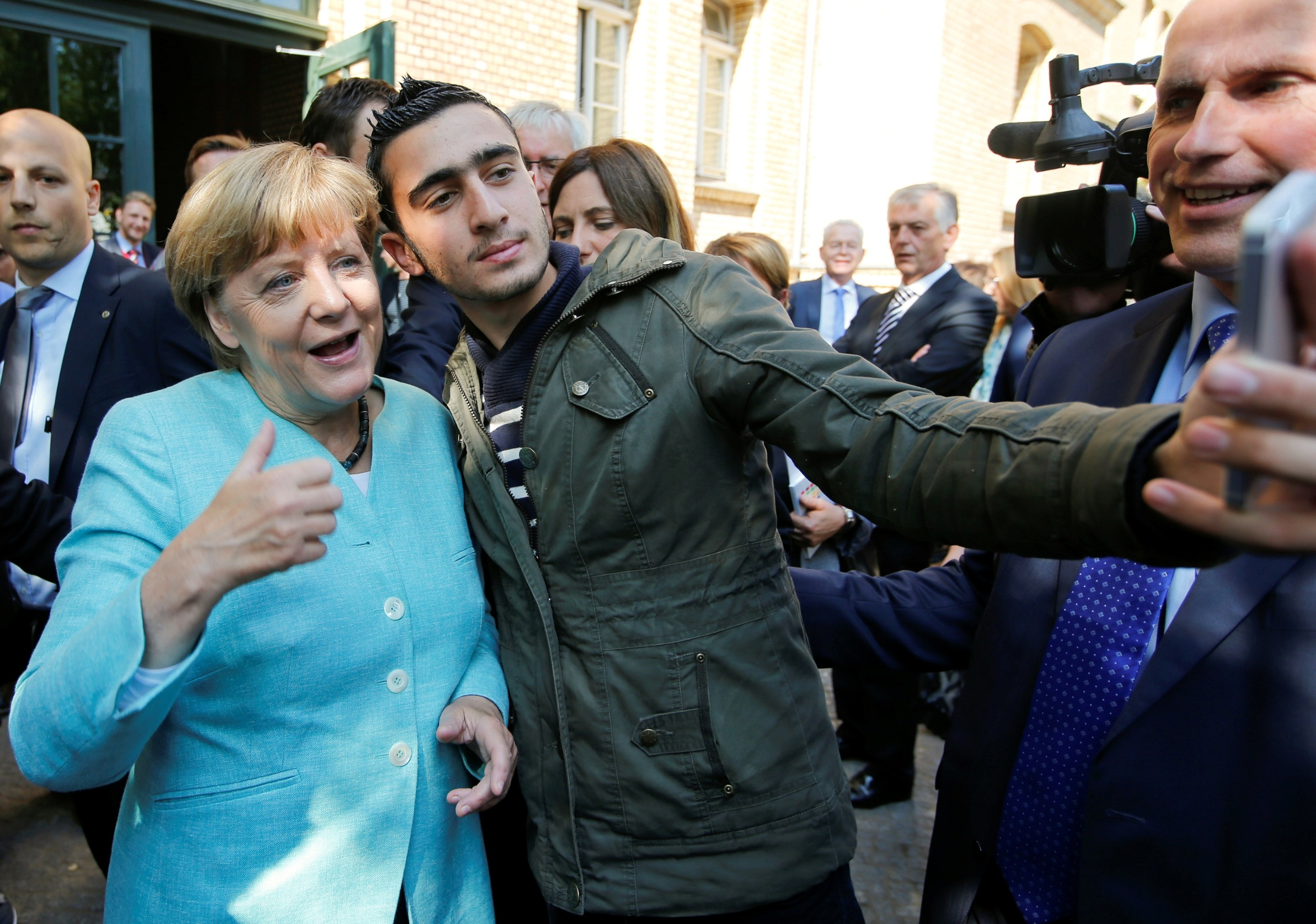 FILE PHOTO: Syrian refugee Anas Modamani takes a selfie with German Chancellor Angela Merkel outside a refugee camp near the Federal Office for Migration and Refugees after registration at Berlin's Spandau district, Germany September 10, 2015.  A German court will on February 6, 2017 hold its first hearing in the case of a Syrian refugee who is suing Facebook after the social networking site declined to remove all posts linking him to crimes and militant attacks.  REUTERS/Fabrizio Bensch/File Photo - RC1CB84EA810