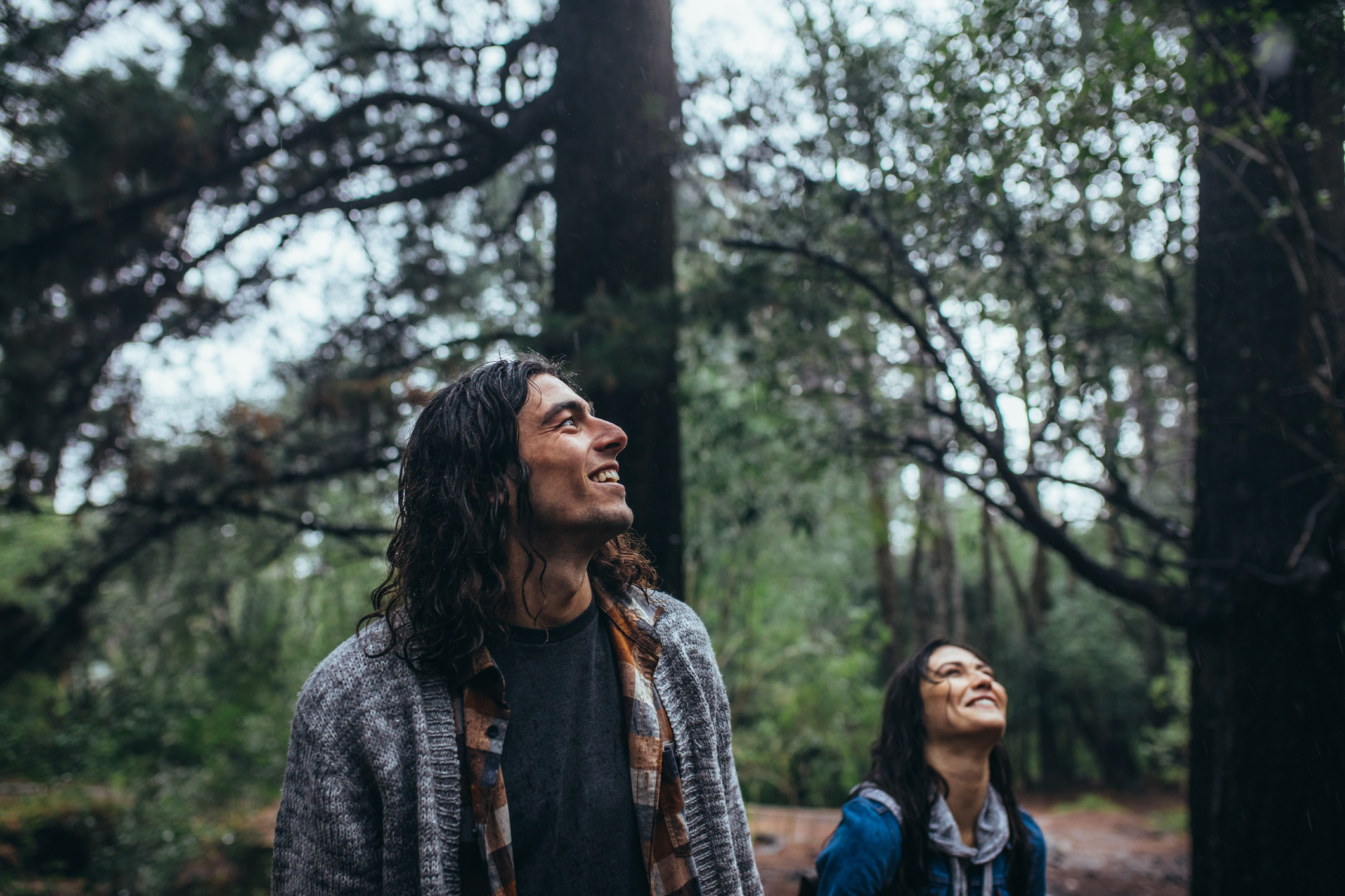 Young man in forest with her girlfriend at the back enjoying the view. Man admiring the nature with woman at back in forest.