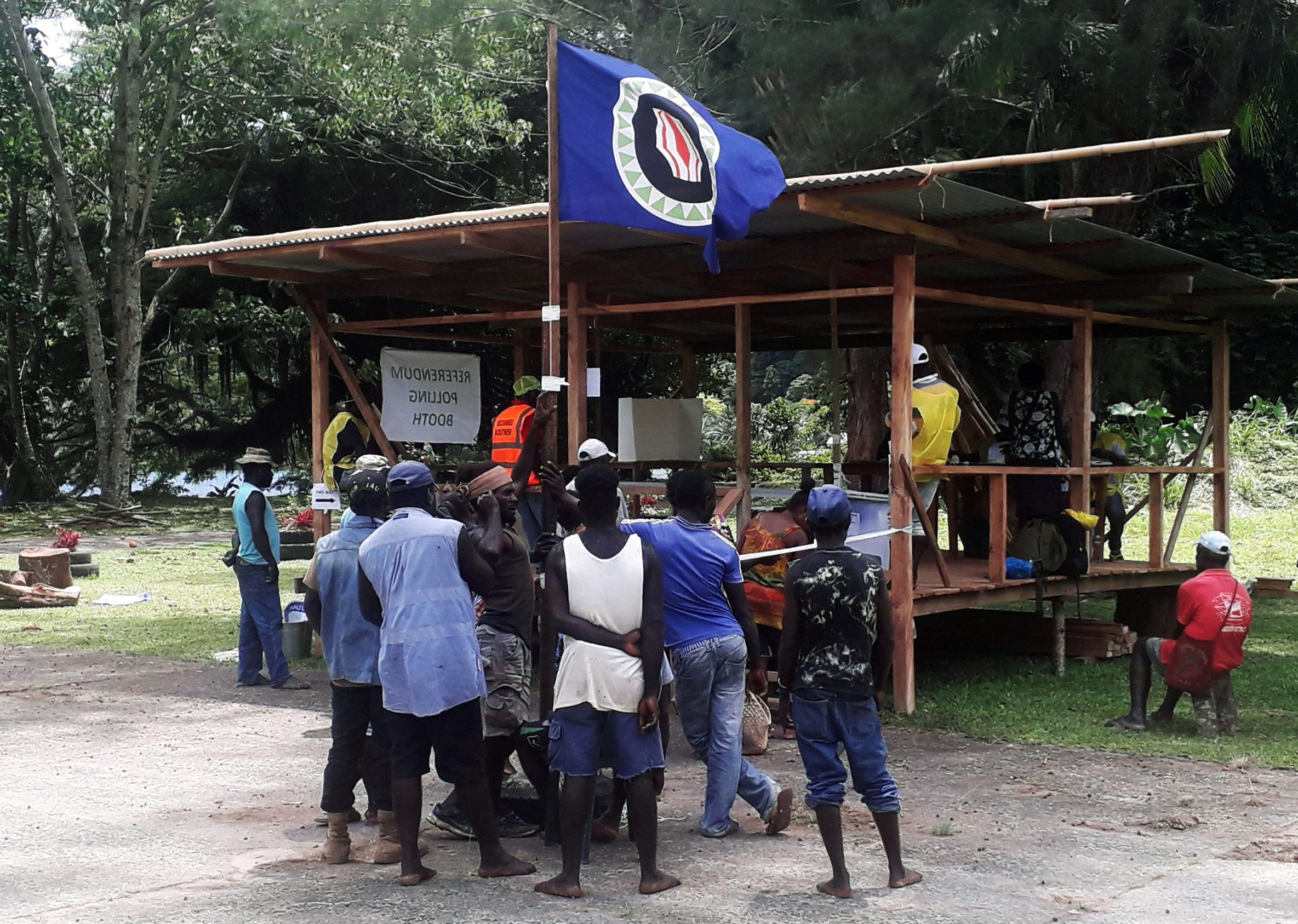 FILE PHOTO: Residents hold a Bougainville flag at a polling station during a non-binding independence referendum in Arawa, on the Papua New Guinea island of Bougainville November 26, 2019.  REUTERS/Melvin Levongo/File Photo