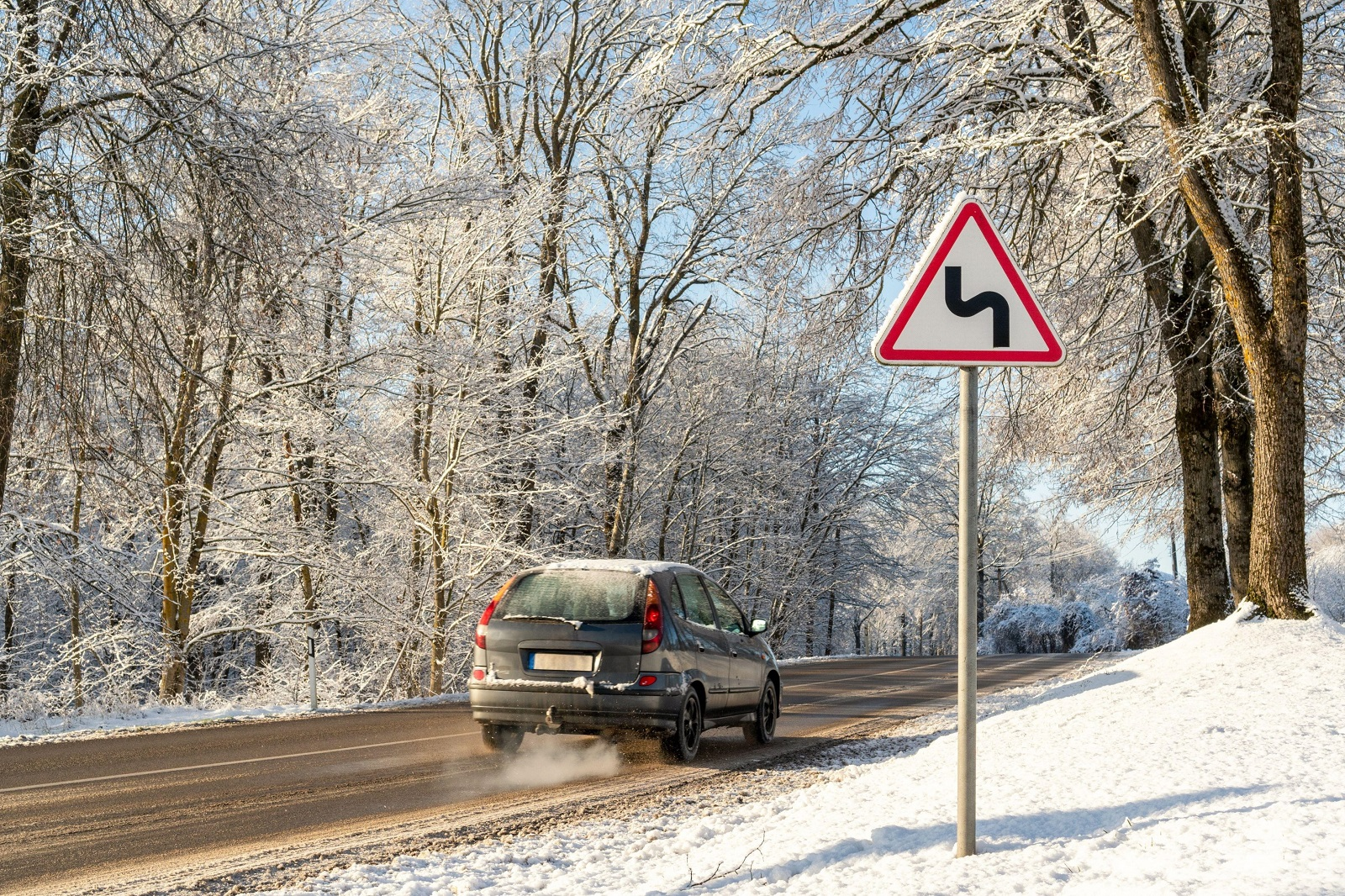 Winter Driving - Curvy Winter Road with Warning Sign. Snow-covered road in winter, car on a dangerous stretch of road covered with snow and ice. Selective focus on road sign., Image: 486276395, License: Royalty-free, Restrictions: , Model Release: no, Credit line: graja / Alamy / Alamy / Profimedia