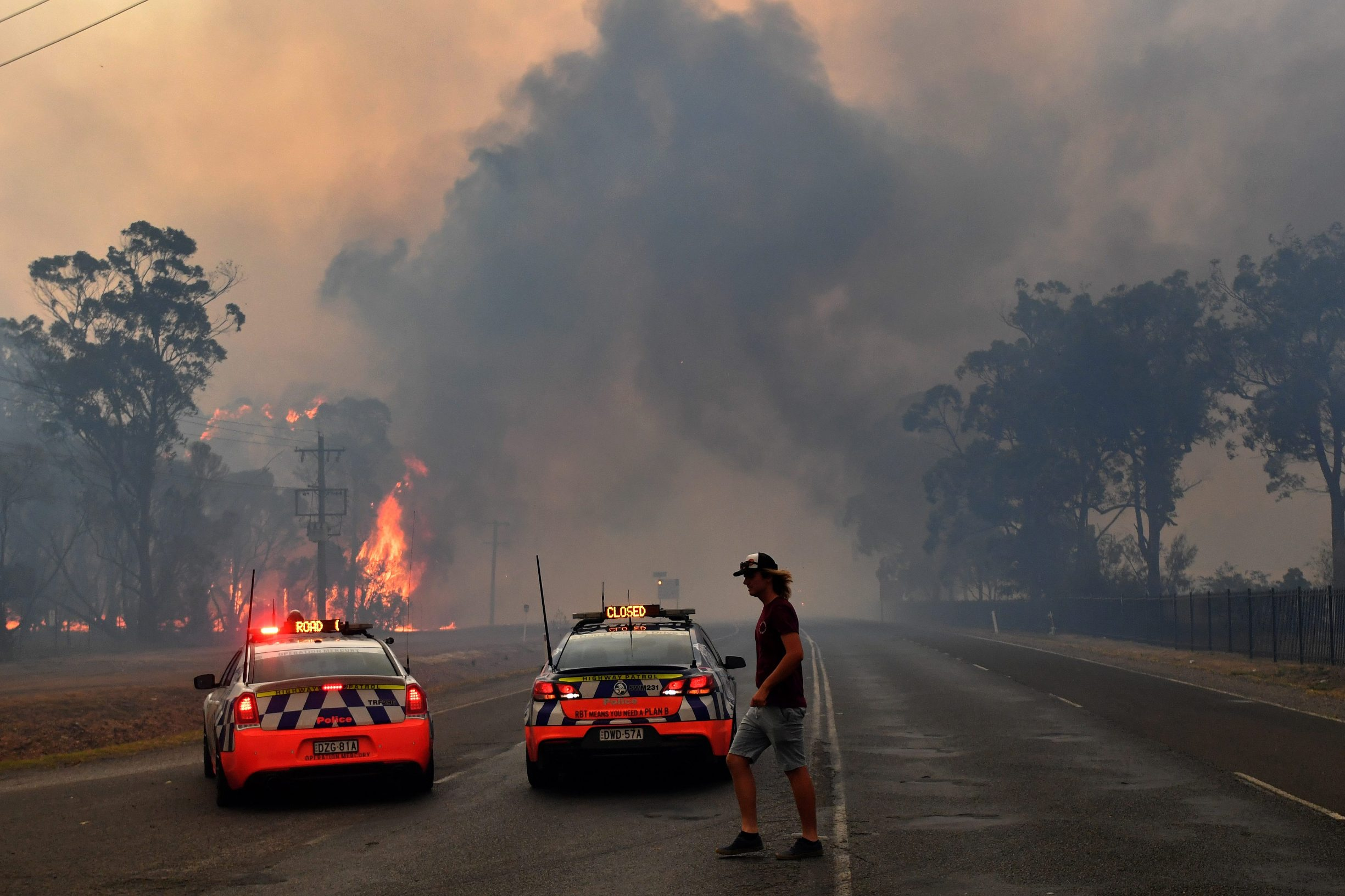 Police block the Old Hume Highway as a blaze jumps the road near the town of Tahmoor as the Green Wattle Creek Fire threatens a number of communities in the south west of Sydney, Australia, December 19, 2019. AAP Image/Dean Lewins/via REUTERS  ATTENTION EDITORS - THIS IMAGE WAS PROVIDED BY A THIRD PARTY. NO RESALES. NO ARCHIVE. AUSTRALIA OUT. NEW ZEALAND OUT. NO COMMERCIAL OR EDITORIAL SALES IN NEW ZEALAND. NO COMMERCIAL OR EDITORIAL SALES IN AUSTRALIA.
