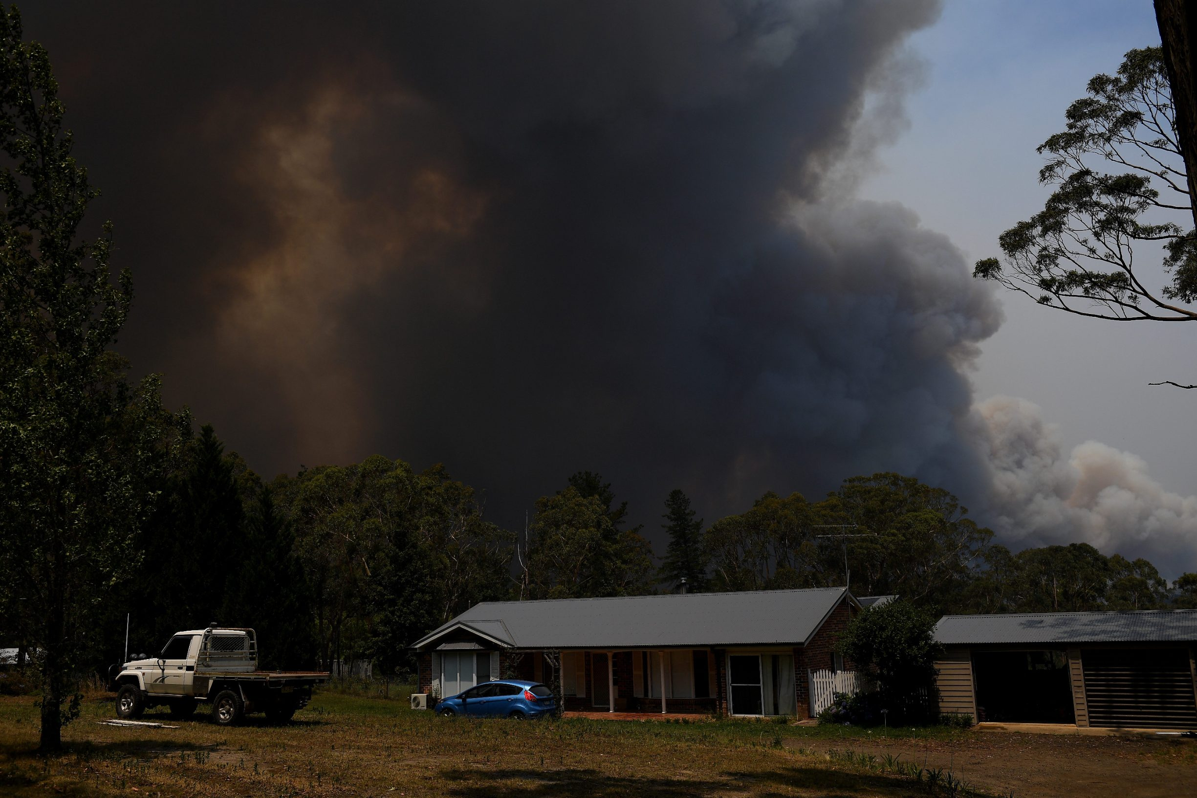 A home is seen as smoke from the Grose Valley Fire rises in the distance, at Bilpin, Saturday, December 21, 2019. Conditions are expected to worsen across much of NSW as temperatures tip 40C. (AAP Image/Dan Himbrechts) NO ARCHIVING    AAP/via REUTERS    ATTENTION EDITORS - THIS IMAGE WAS PROVIDED BY A THIRD PARTY. NO RESALES. NO ARCHIVE. AUSTRALIA OUT. NEW ZEALAND OUT. NO COMMERCIAL OR EDITORIAL SALES IN NEW ZEALAND. NO COMMERCIAL OR EDITORIAL SALES IN AUSTRALIA.