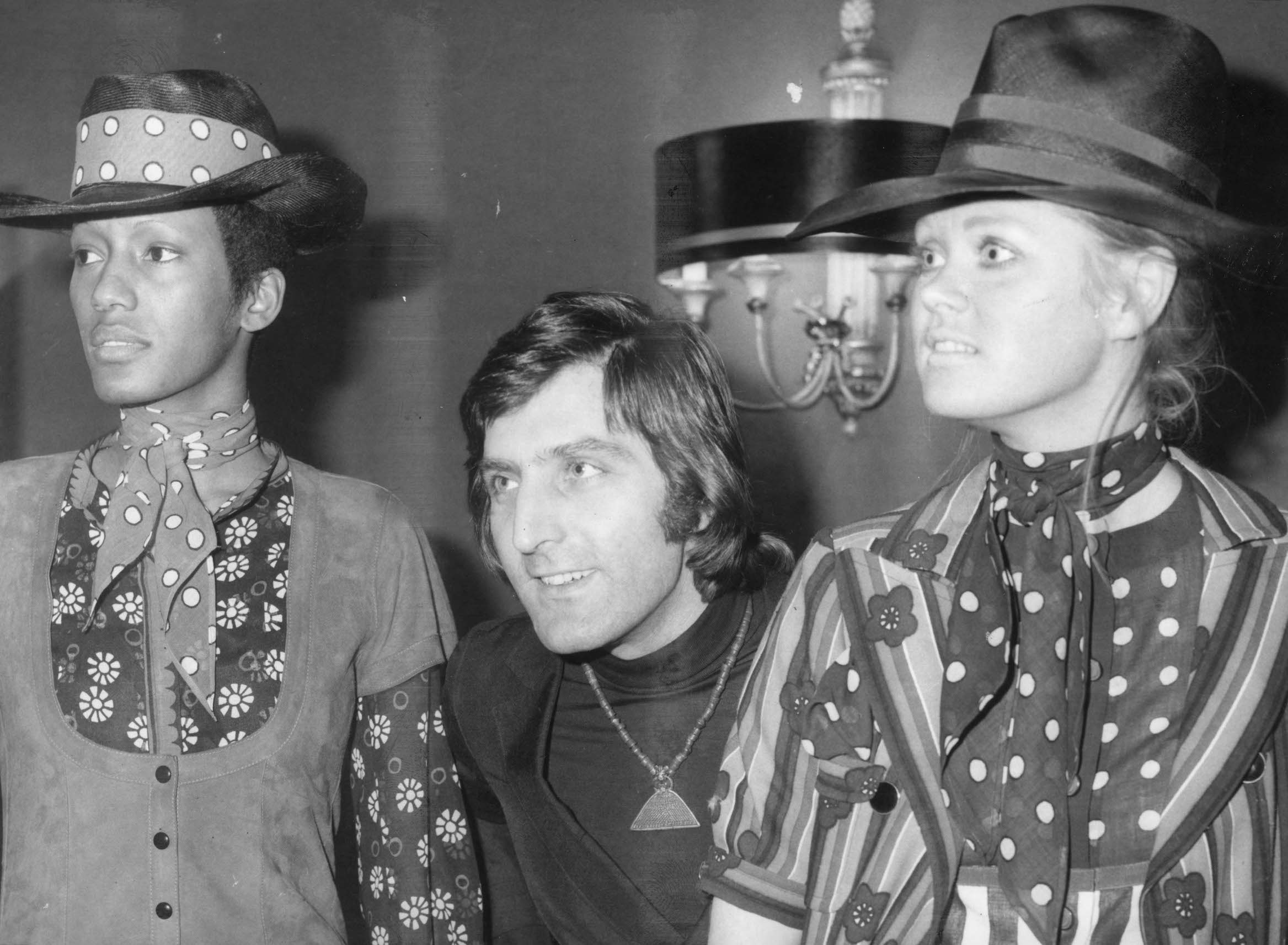 French couturier Emanuel Ungaro with two of his models wearing flower power daisy motifs, gypsy-style scarves and tall hats.    (Photo by Central Press/Getty Images)