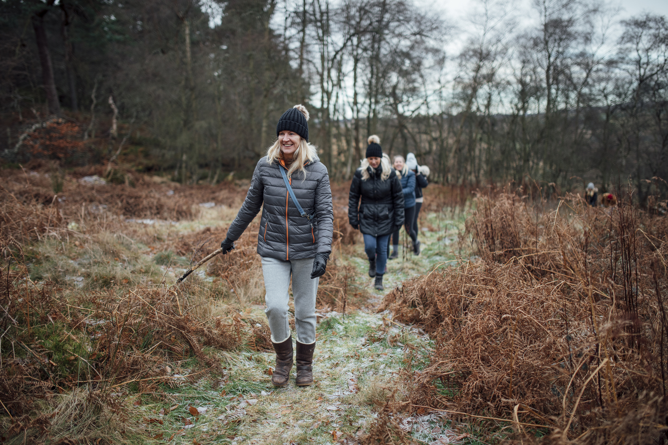 Four women are enjoying a walk through the woodland together in winter.
