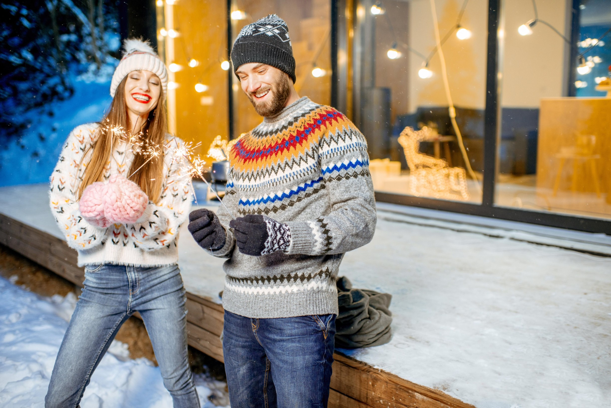 Young happy couple dressed in sweaters celebrating winter holidays with bengal fire in front of a beautiful decorated house, Image: 403492188, License: Royalty-free, Restrictions: , Model Release: yes, Credit line: RossHelen editorial / Alamy / Alamy / Profimedia