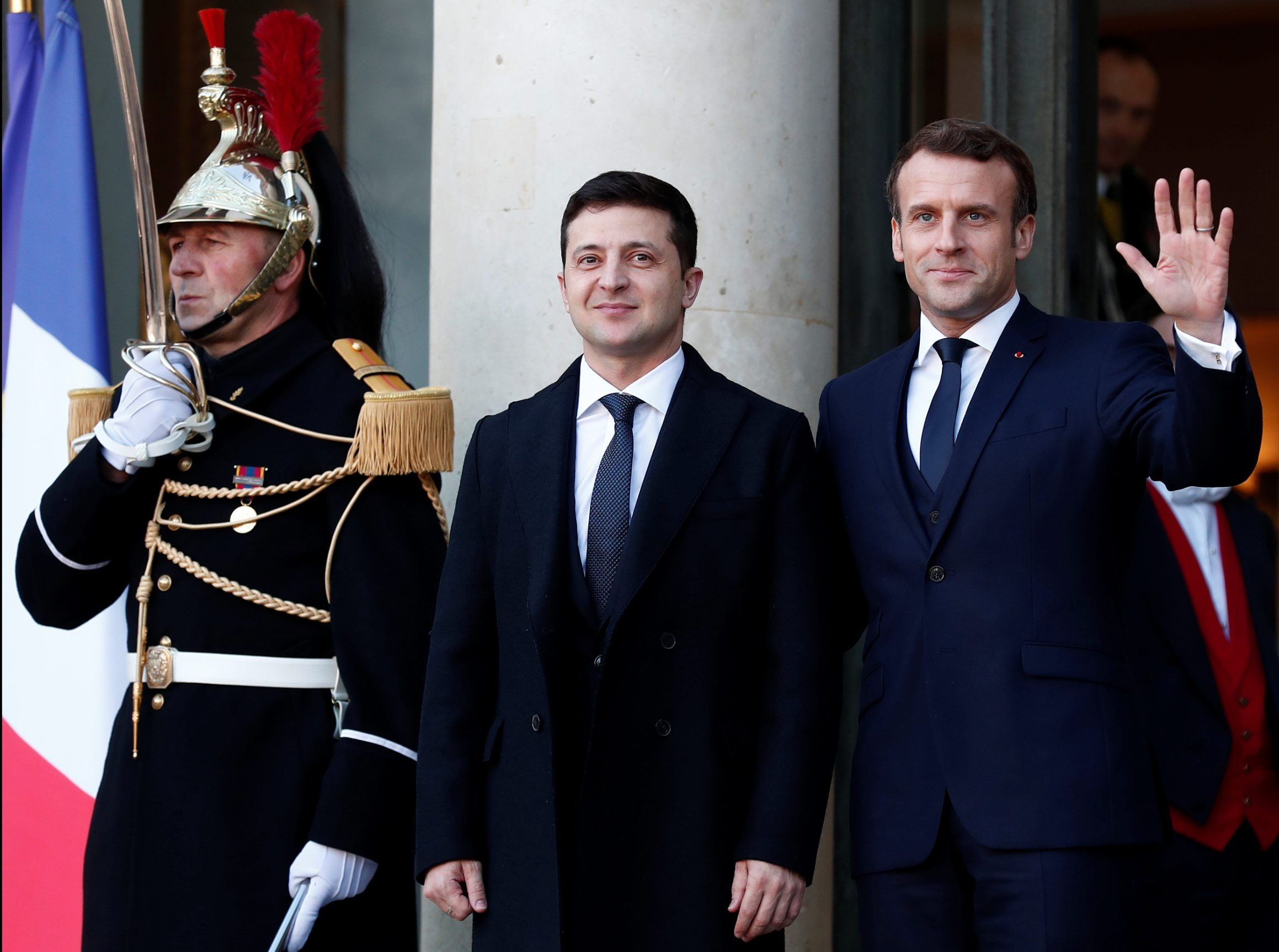 French President Emmanuel Macron (R) greets Ukrainian President Volodymyr Zelensky (L) as he arrives to attend a summit on Ukraine at the Elysee Palace in Paris, France December 9, 2019. German Chancellor Merkel, French President Macron, Ukrainian President Zelensky and Russian President Putin took part in the summit.  Ian Langsdon/Pool via REUTERS