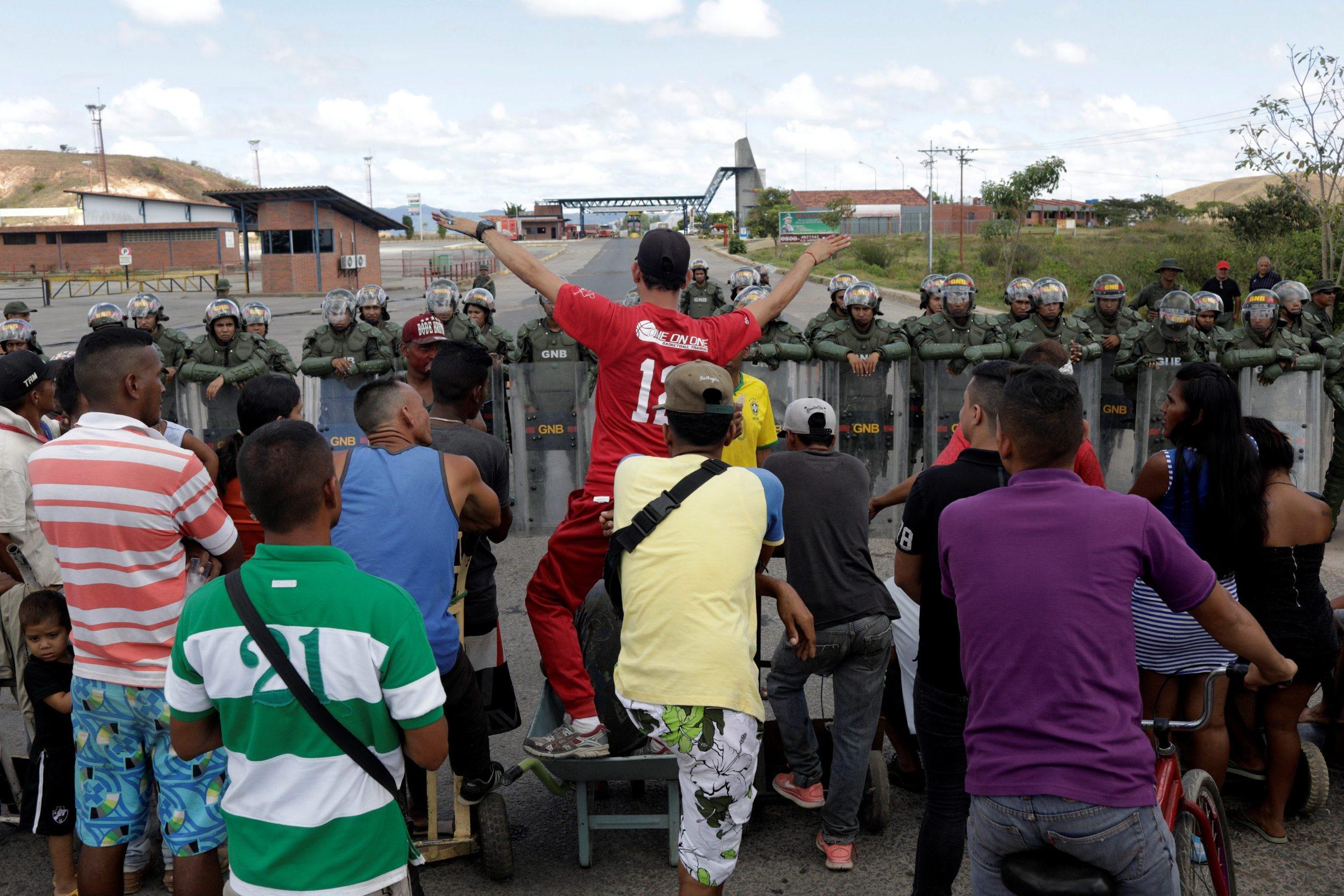 People waiting to cross to Venezuela stand opposite Venezuelan National guards at the border between Venezuela and Brazil in Pacaraima, Roraima state, Brazil, February 22, 2019. REUTERS/Ricardo Moraes